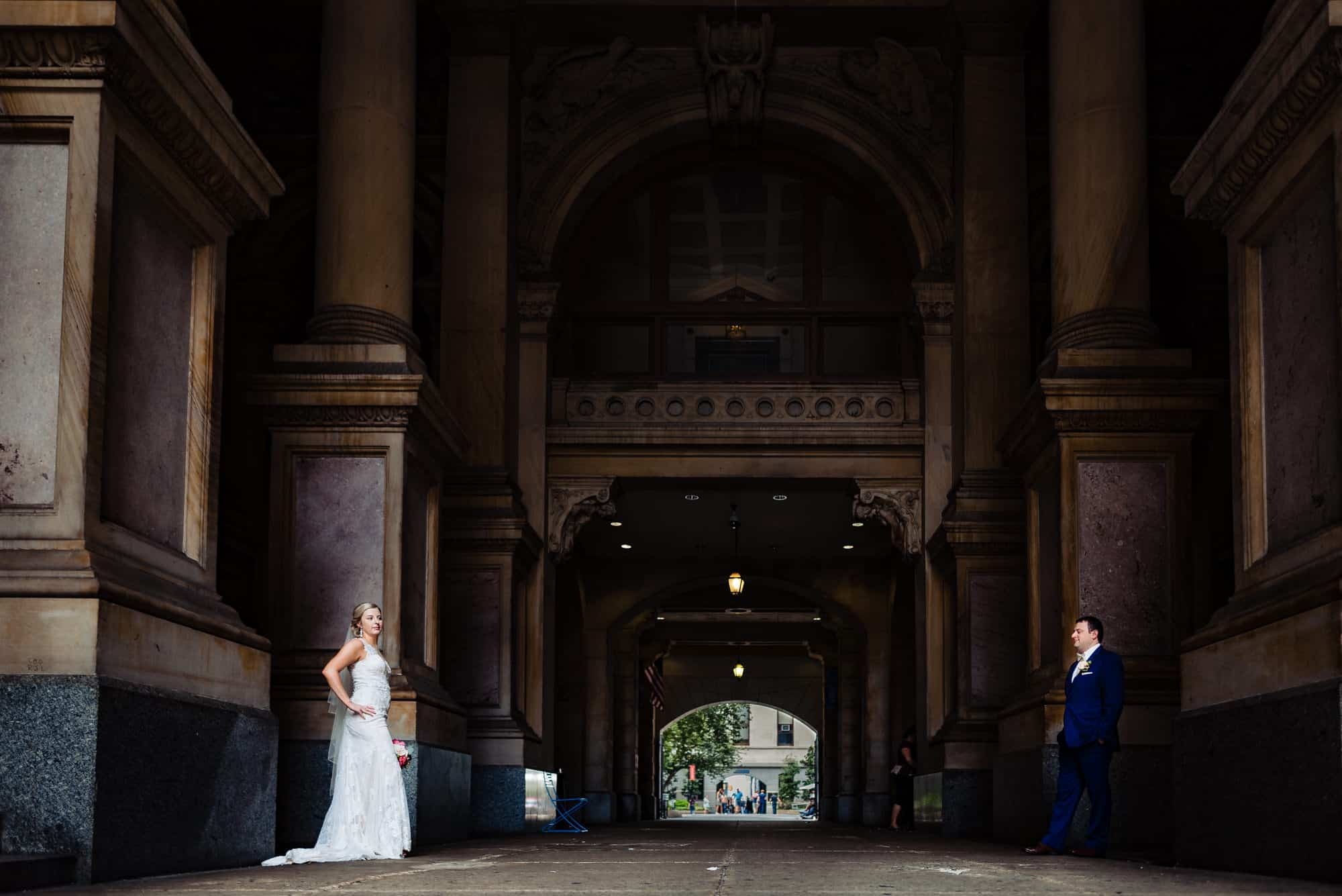 wedding day, bride and groom in old historic building face each other on opposite sides of the walls