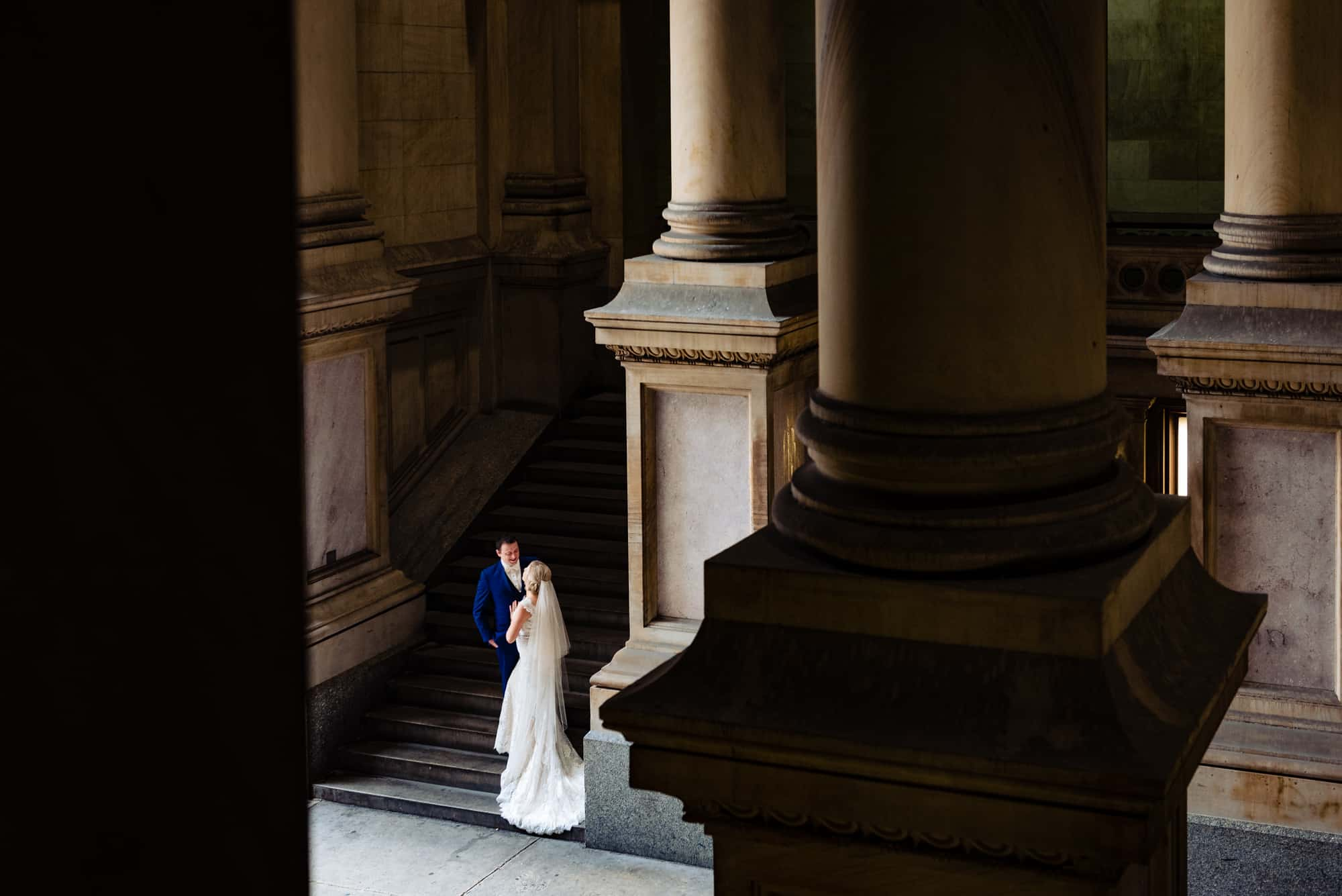 wedding day, far away shot of bride and groom in staircase talking to each other