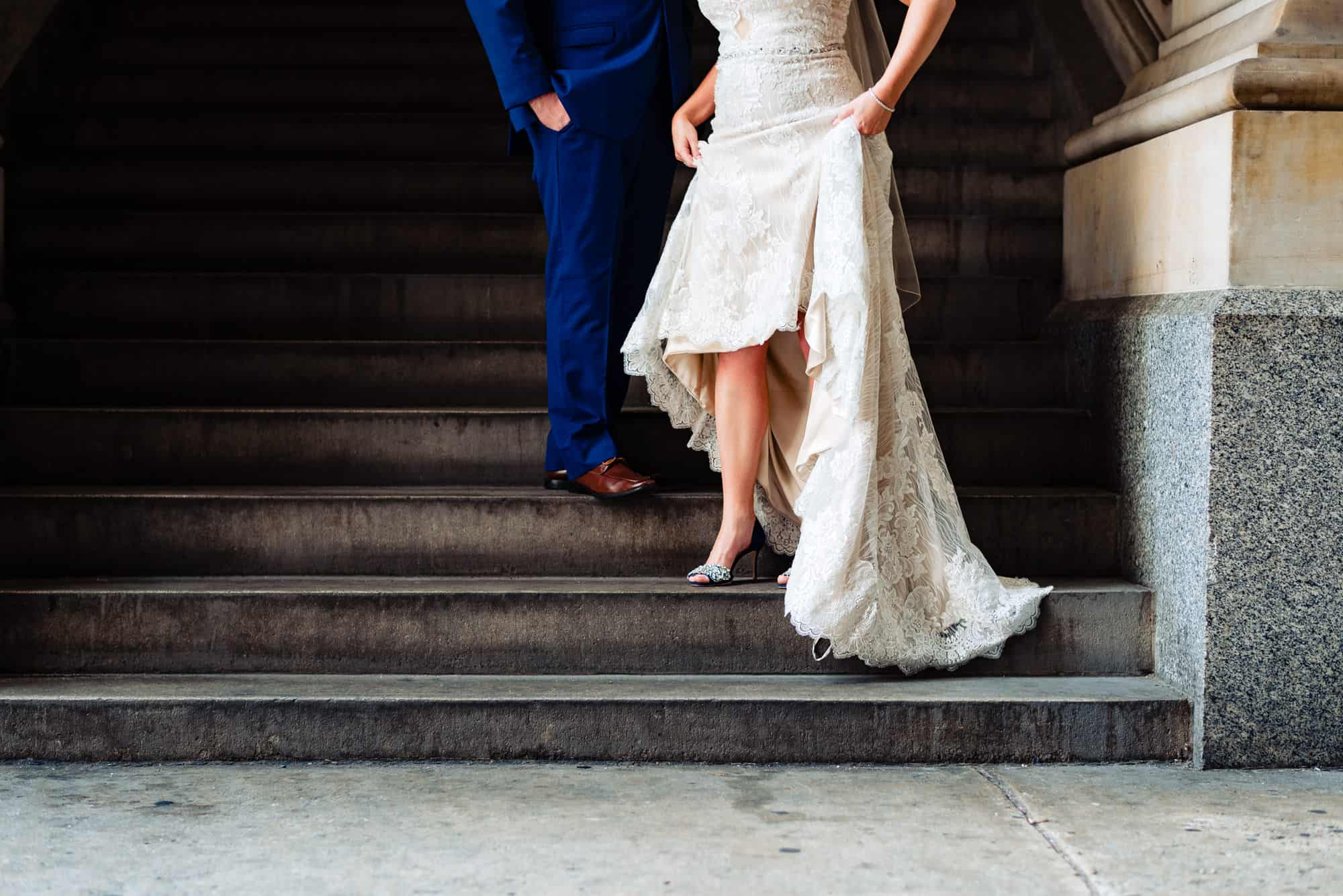 wedding day, shot of the bottom half of the bride and groom while bride is showing off her shoes holding her dress above her knees