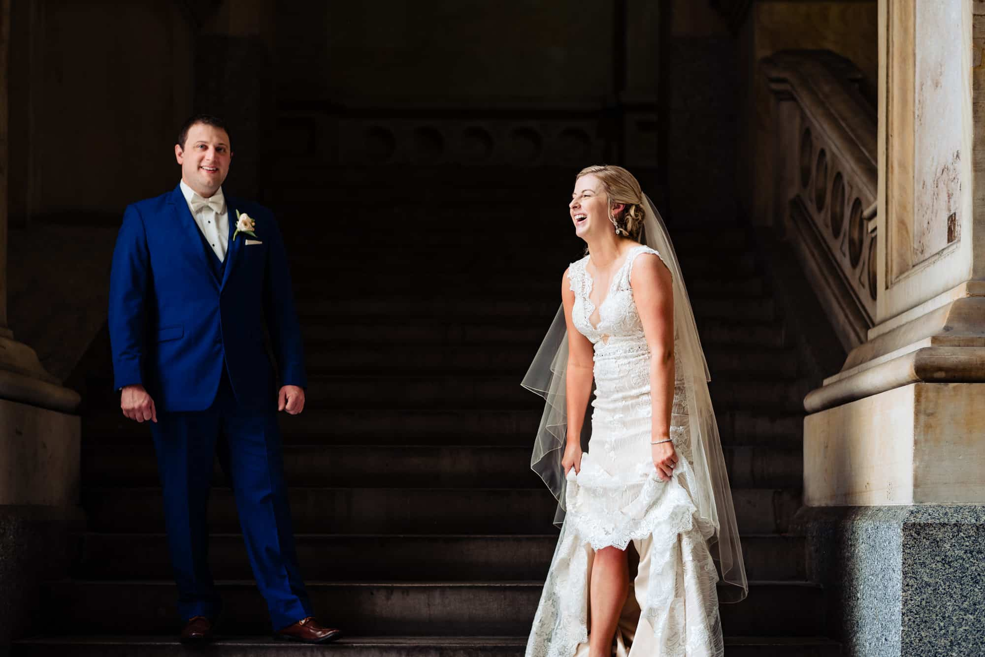wedding day, bride laughing at groom in staircase while holding dress above her knees