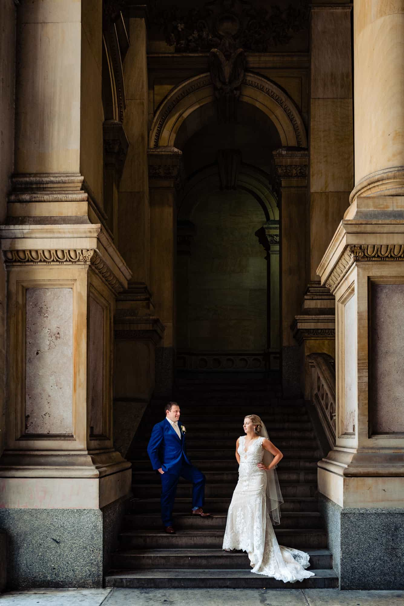 wedding day, bride and groom talking and posing in stair case