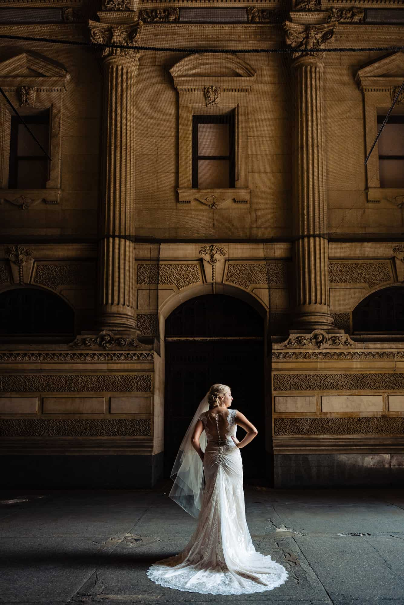 bridal photos, back view of bride in a Maggie Sottero bridal gown against a old building