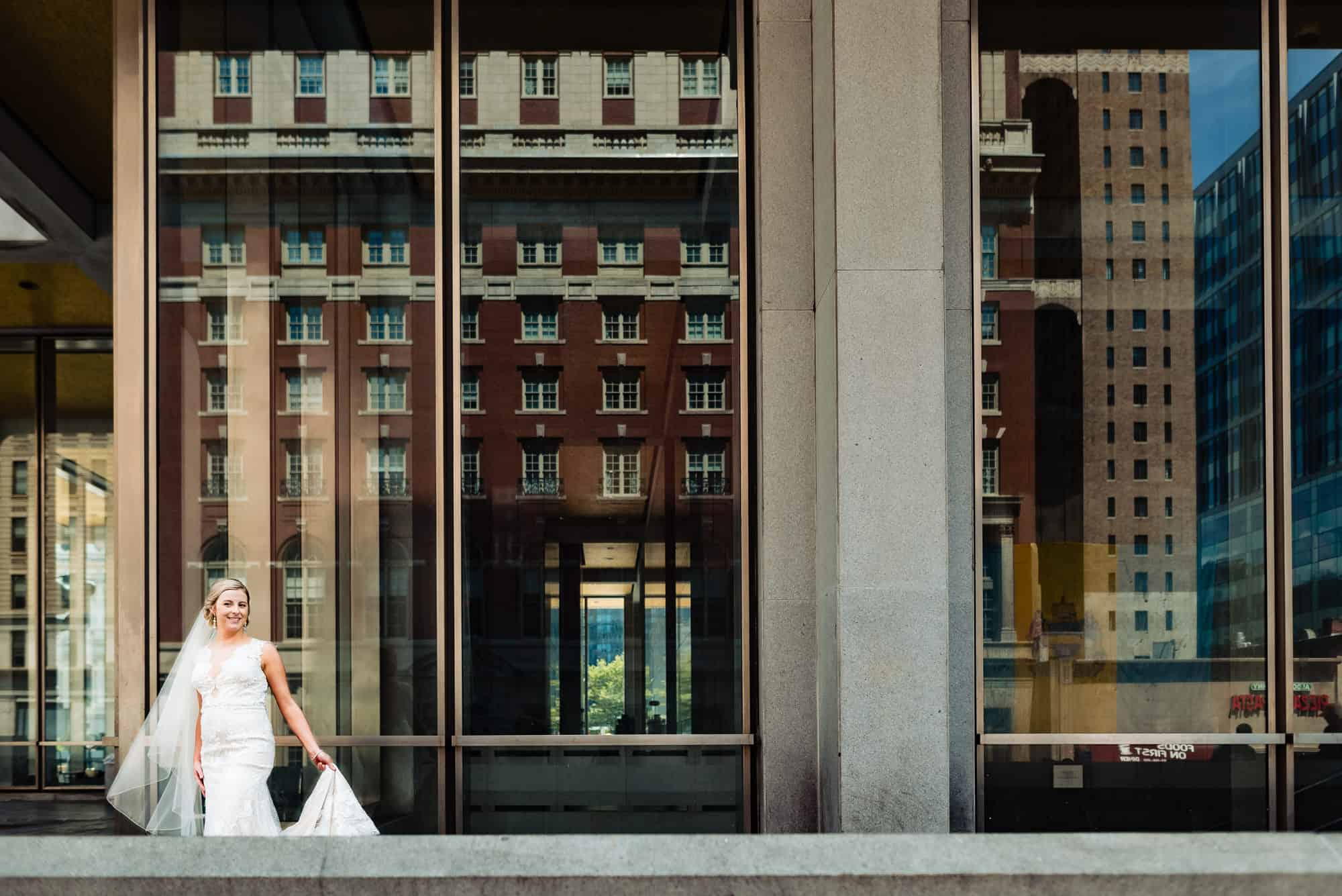 bridal photos, bride hold train of Maggie Sottero gown in front of window