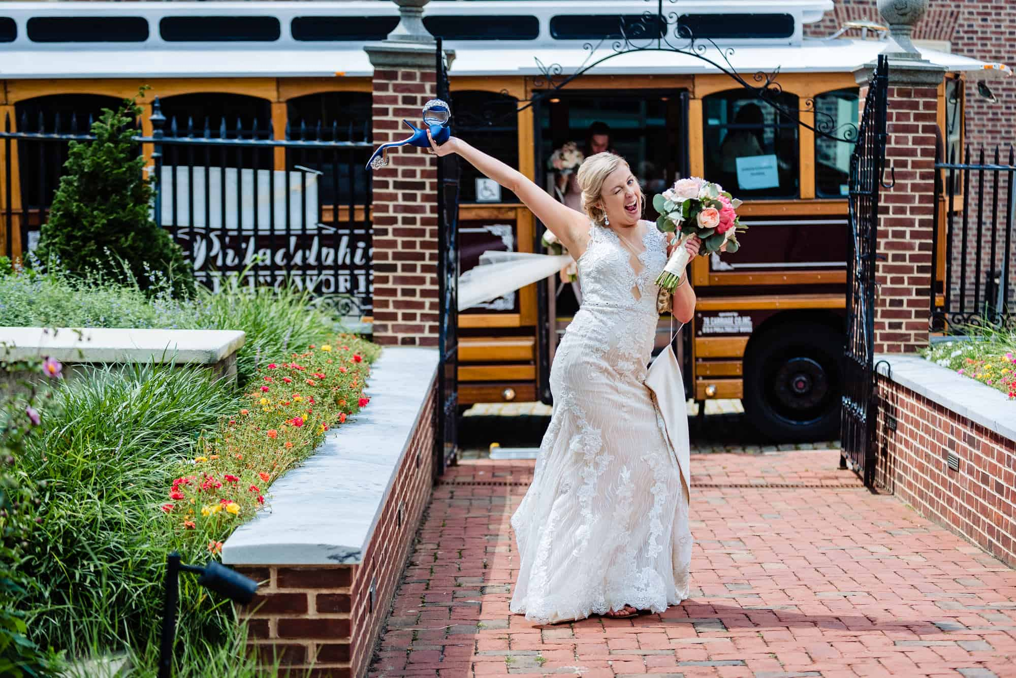 wedding ceremony, bride getting off trolley making funny face with shoes in her hand and arm in the air