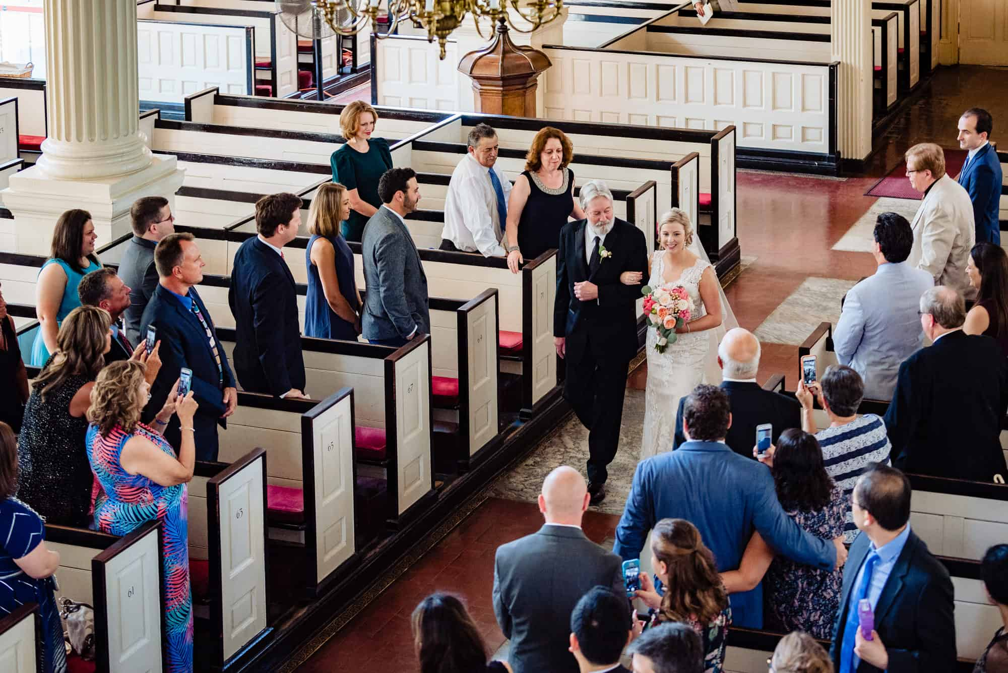 wedding ceremony, overview of guests watching bride walk down the aisle with father