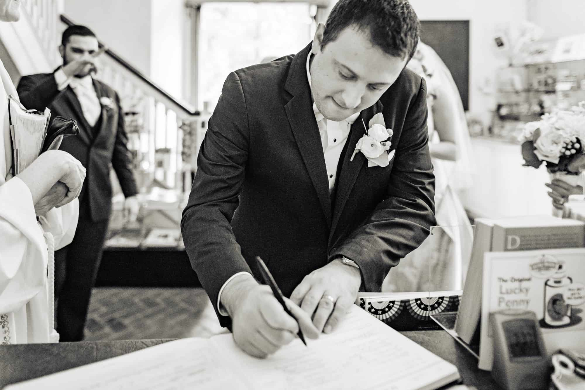 wedding day, groom signing book in lobby after ceremony