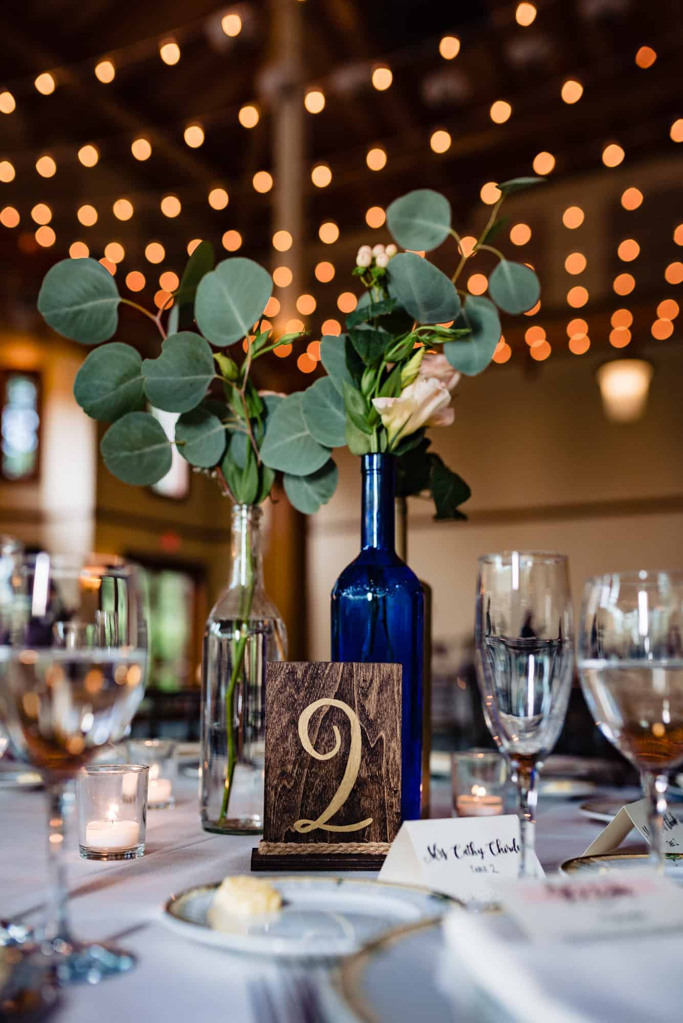 wedding accessories, centerpieces and table number with glasses of wine and champagne