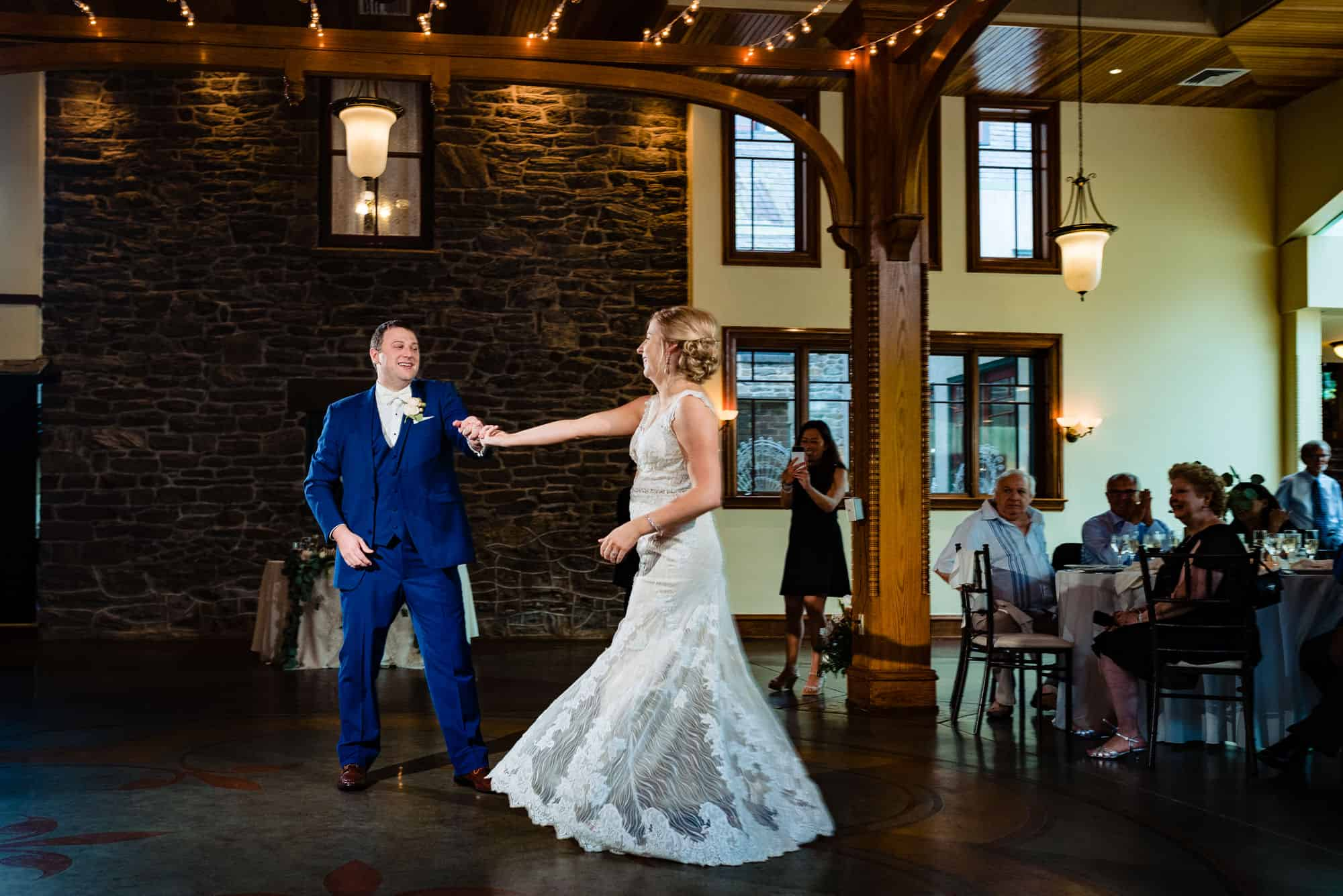 wedding reception, groom twirling bride during first dance in front of guests