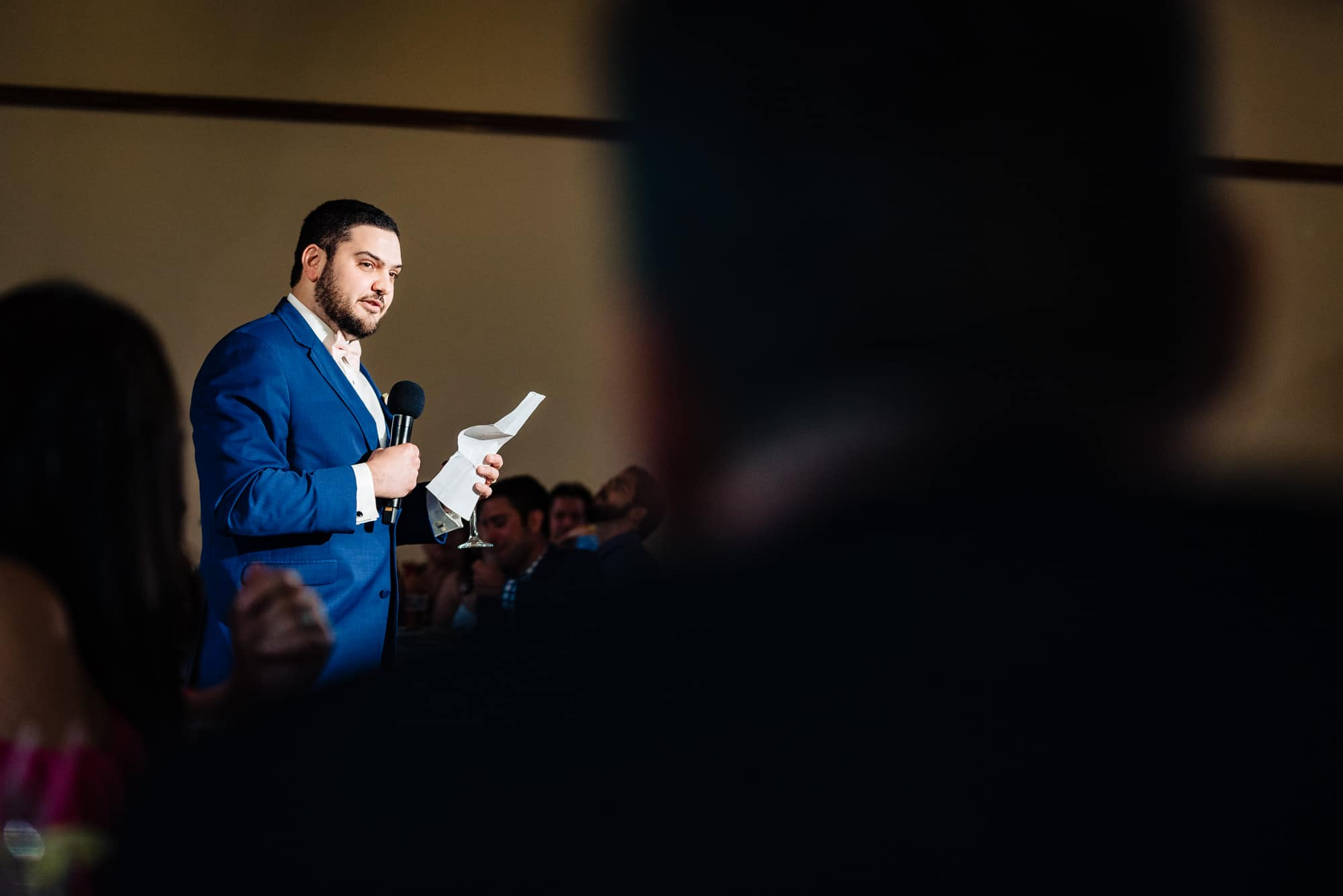 wedding reception, groomsmen hold microphone making a speech