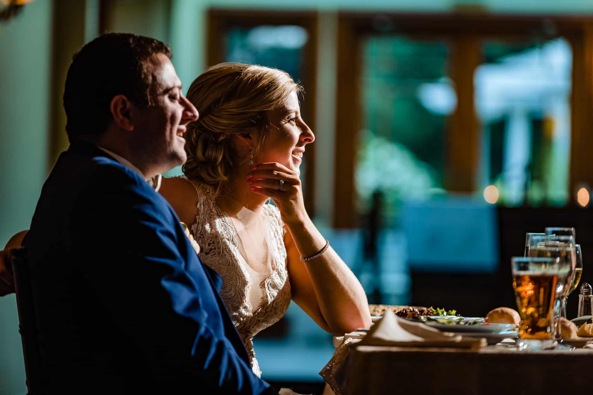 wedding reception, side profile of bride and groom smiling at guests