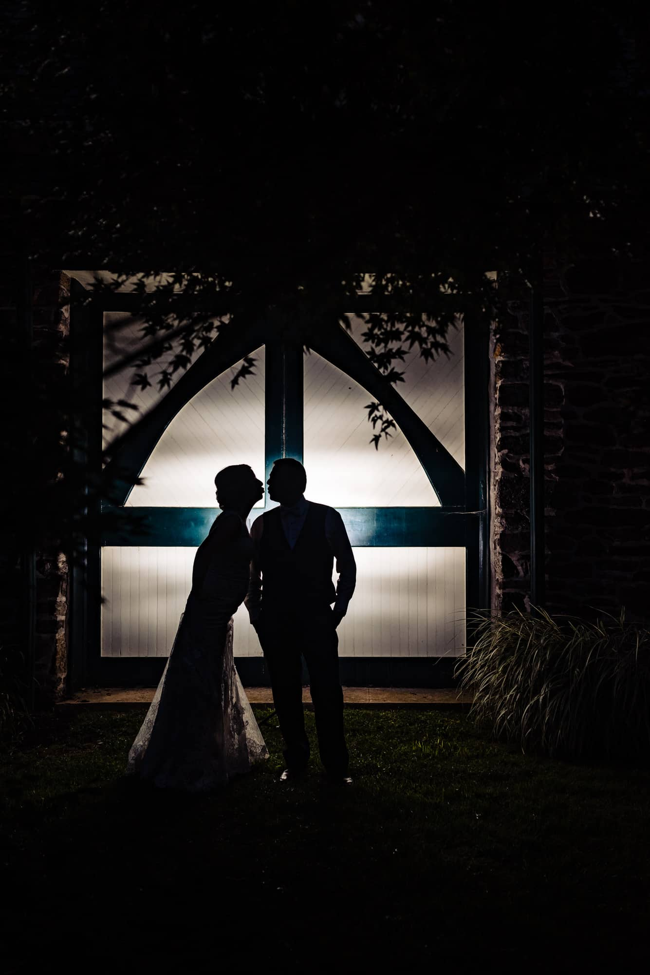 wedding day, silhouette of bride and groom about to kiss in front of two doors