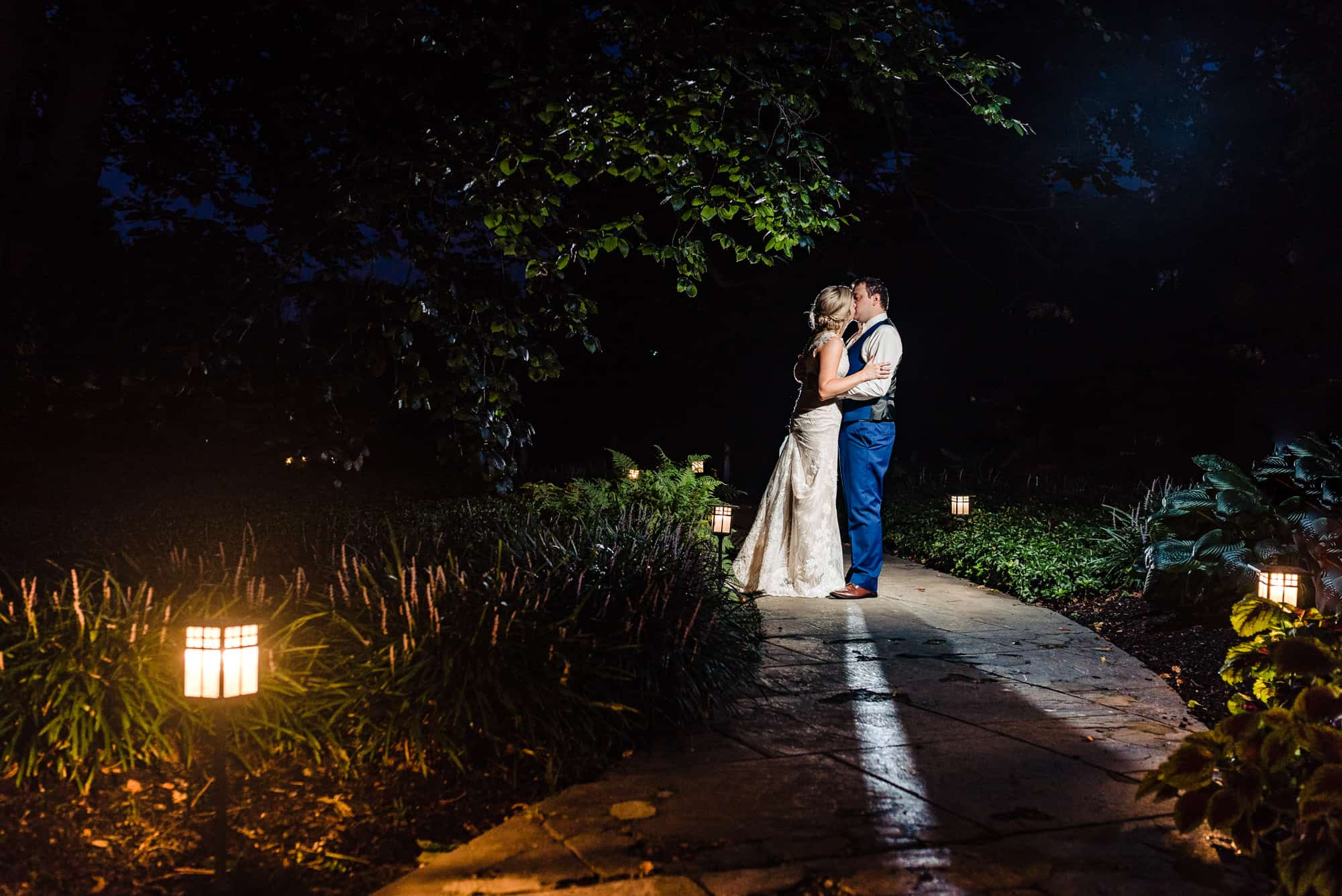 wedding day, bride and groom kissing outside on a pathway between trees