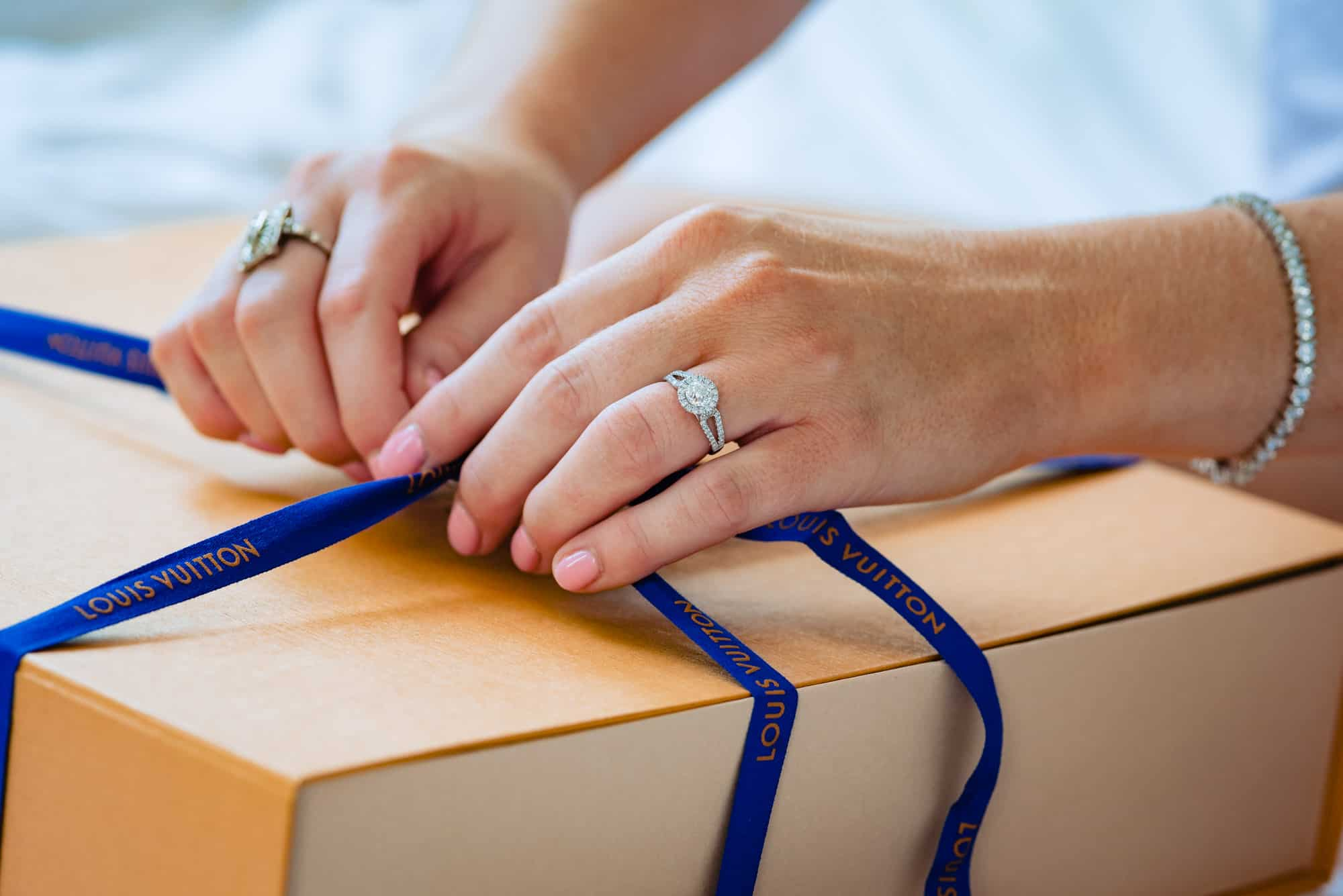 getting ready, close up of brides engagement ring and hands while opening up a Louis Vuitton present box