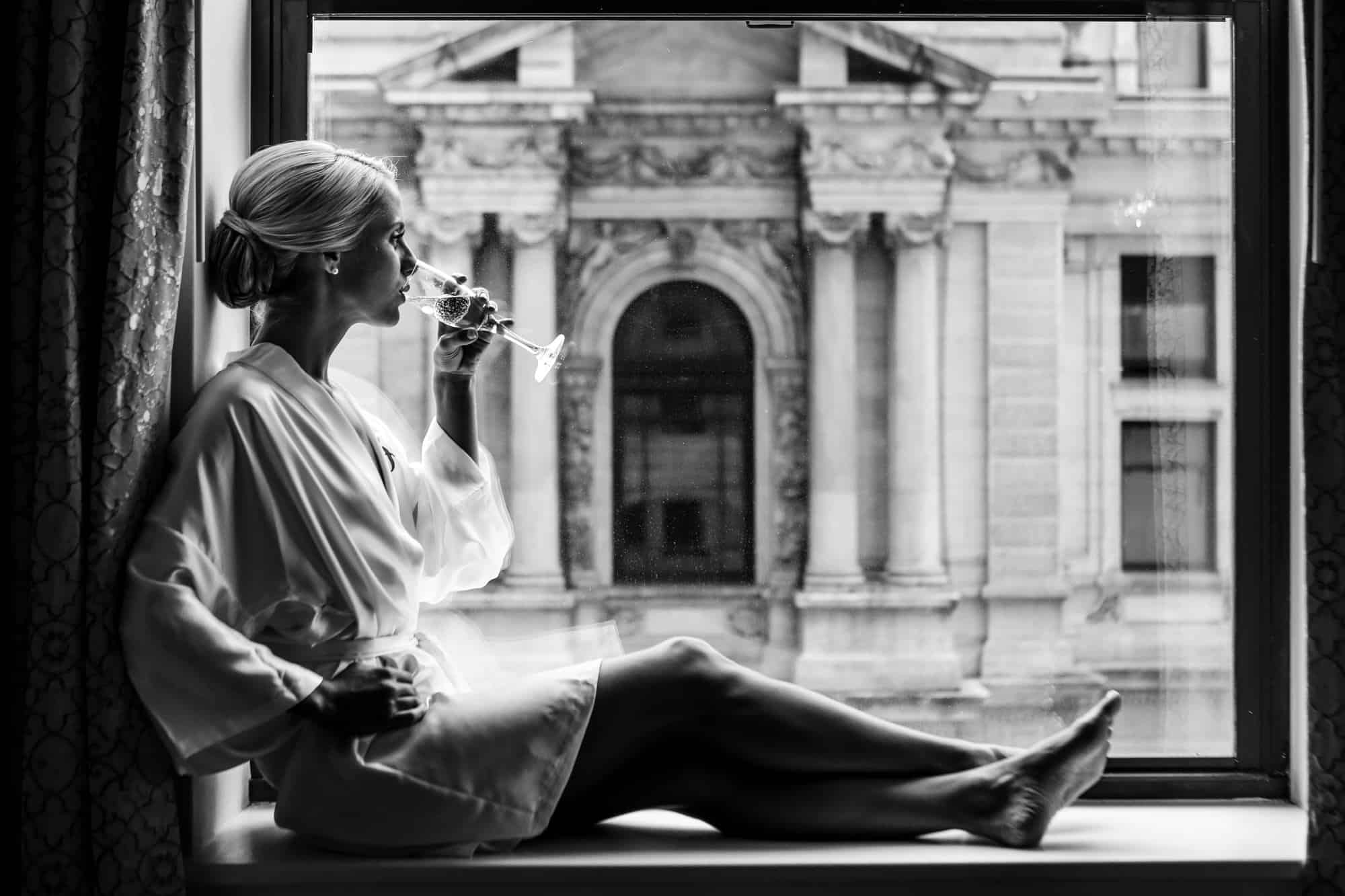 Ritz Carlton Philadelphia Wedding|bride sitting in window sill in robe drinking champagne