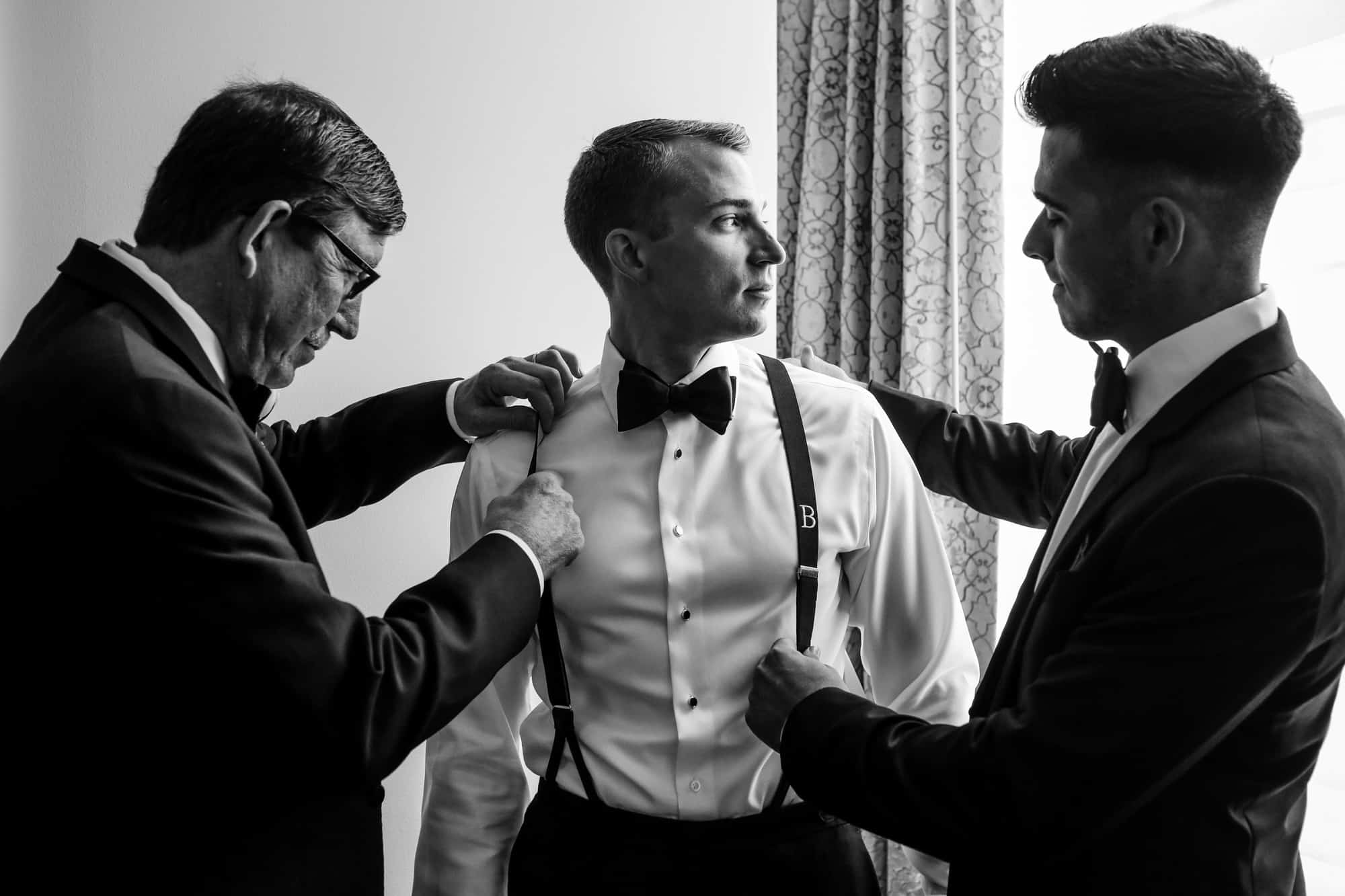 Ritz Carlton Philadelphia Wedding|groom looking out window while best man and father adjust his suspenders