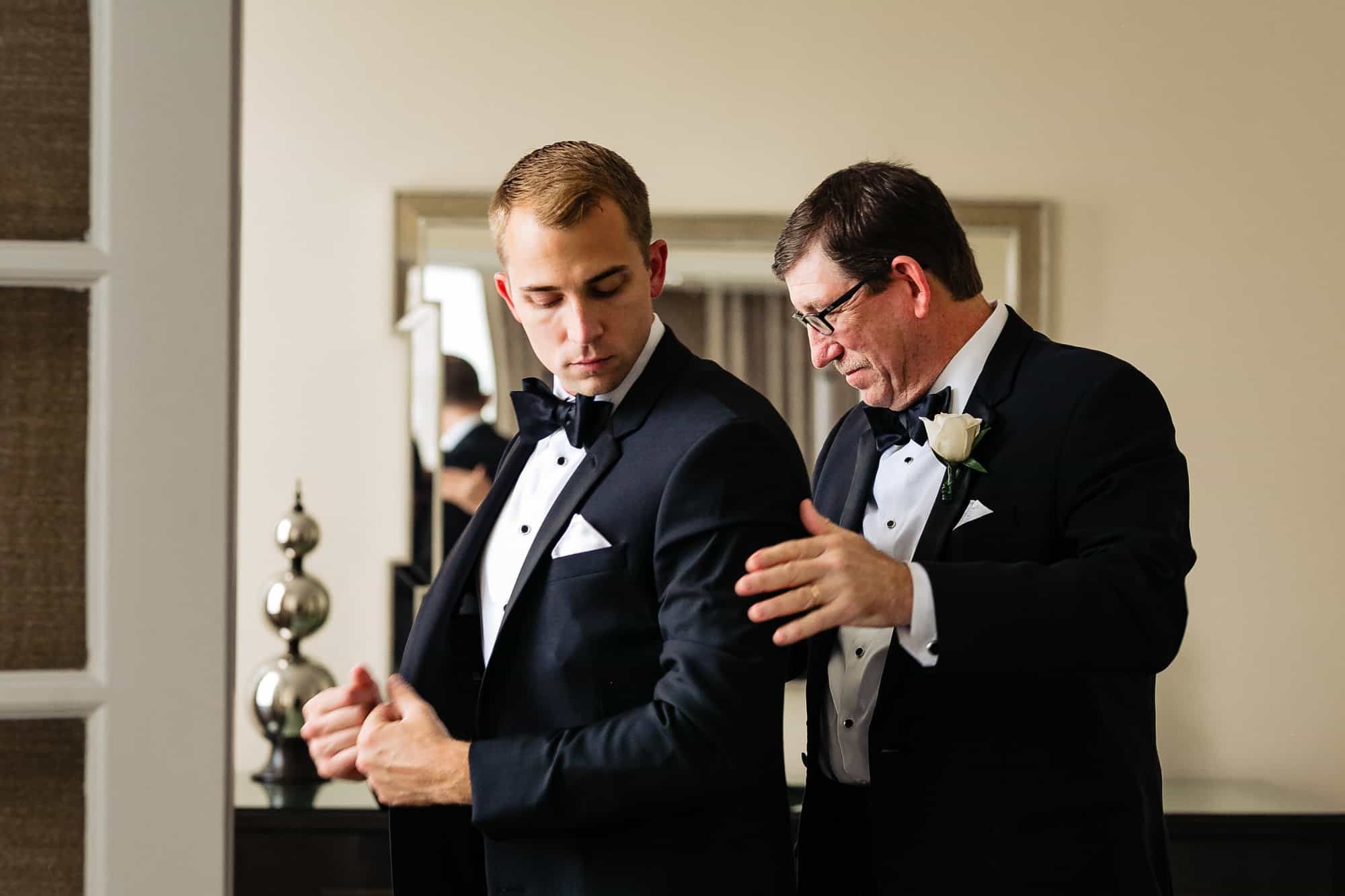 Ritz Carlton Philadelphia Wedding|grooms father helping groom put on suit jacket
