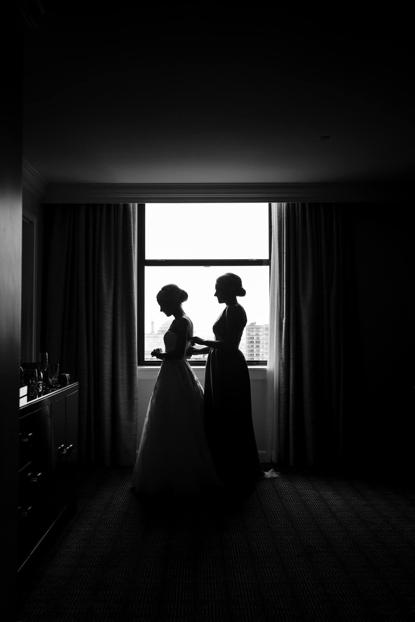 Ritz Carlton Philadelphia Wedding|silhouette of bride being zipped up by her sister