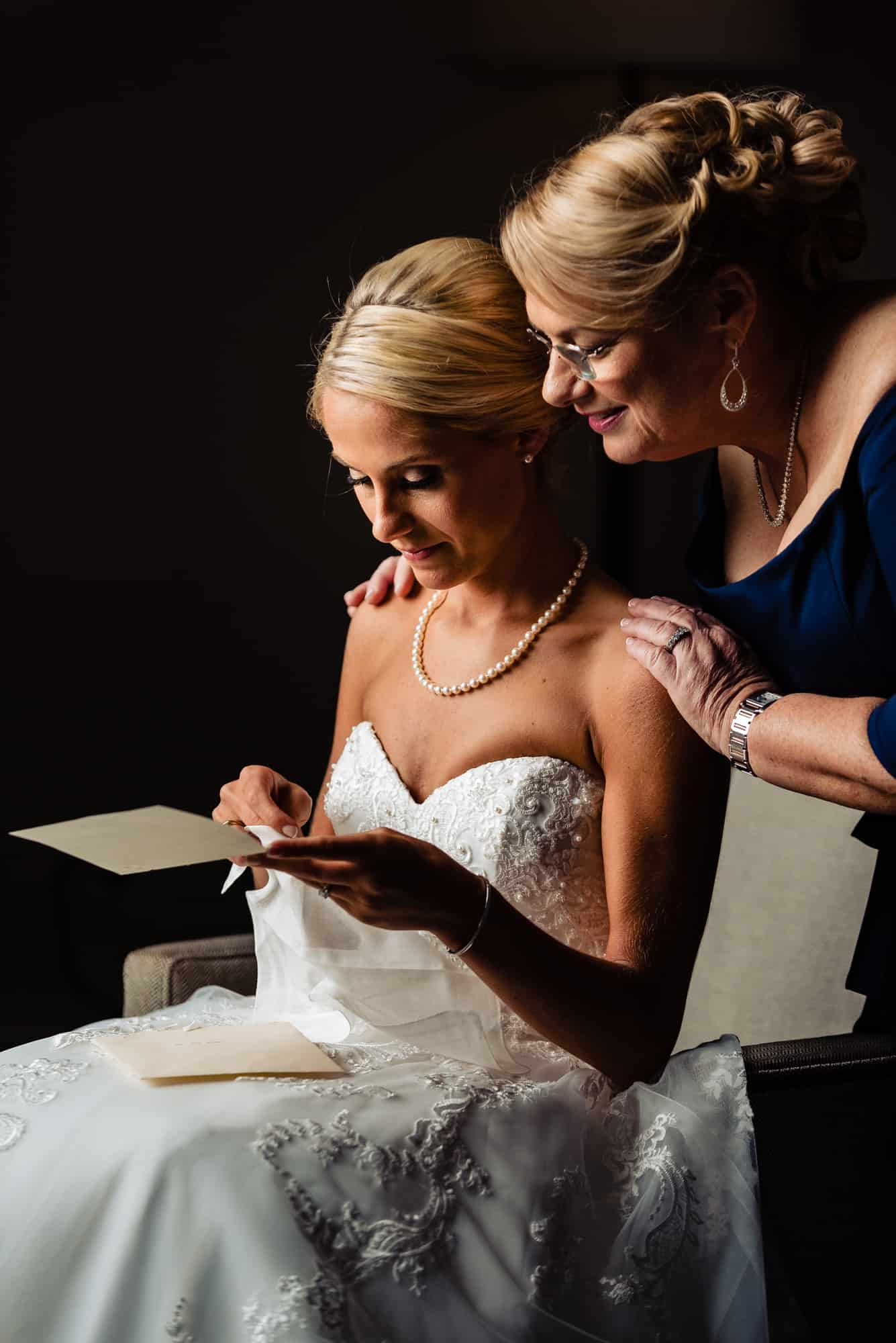 Ritz Carlton Philadelphia Wedding|mother of the bride looking over brides shoulder while she reads letter from groom
