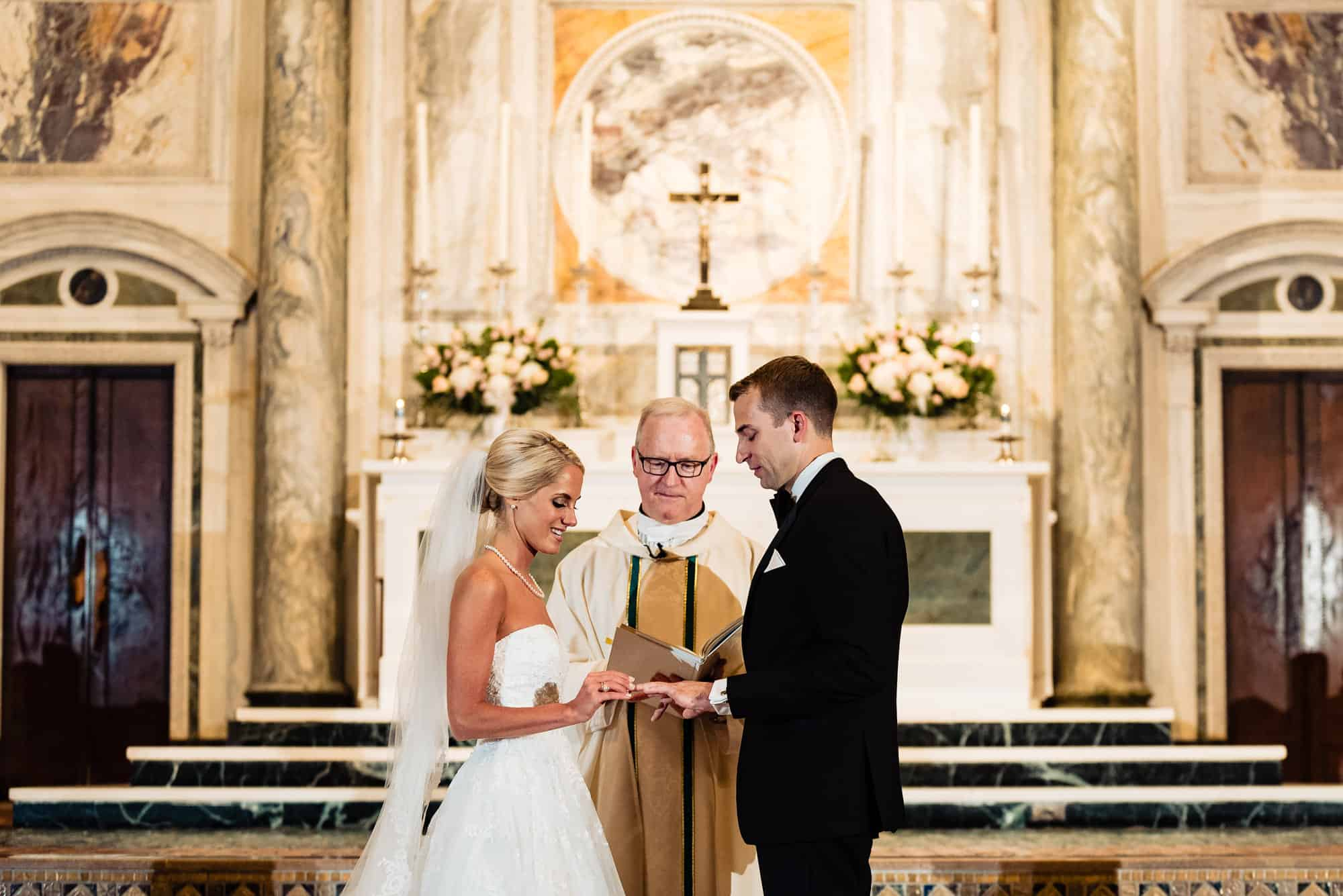 St. Patricks Church|bride putting ring on grooms finger