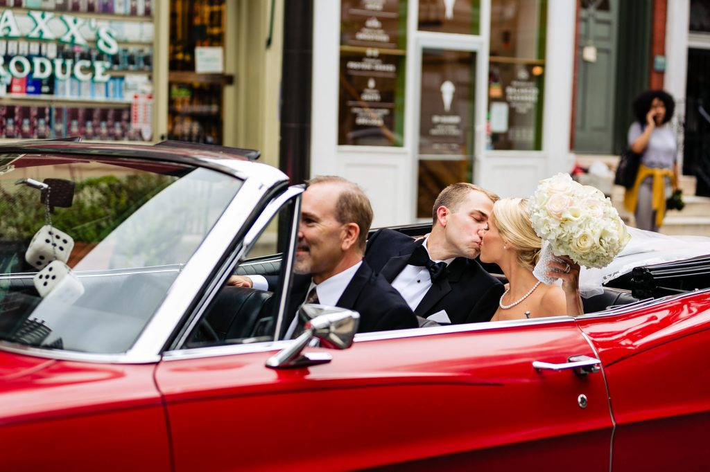 Ritz Carlton Philadelphia Wedding|bride and groom in back seat of red sportscar kissing