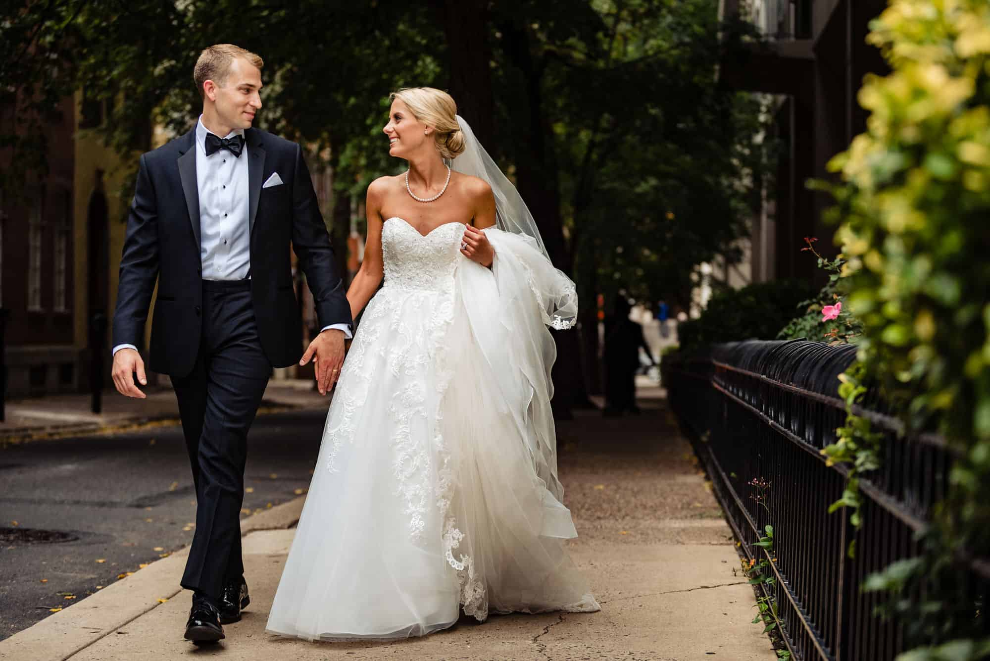 Ritz Carlton Philadelphia Wedding|bride and groom holding hands walking down street