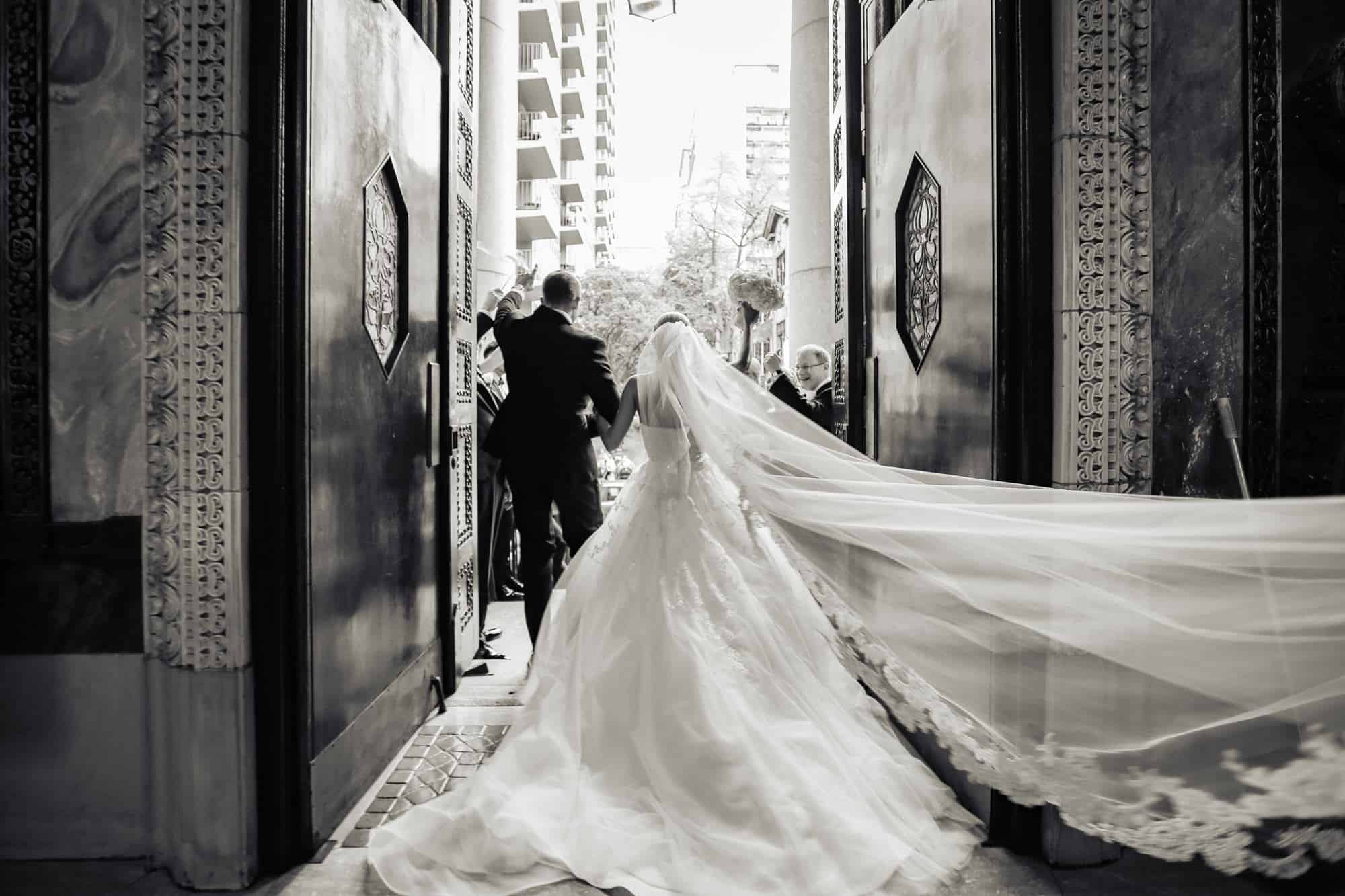St. Patricks Church|bride and groom exiting church waving to guests shot from behind