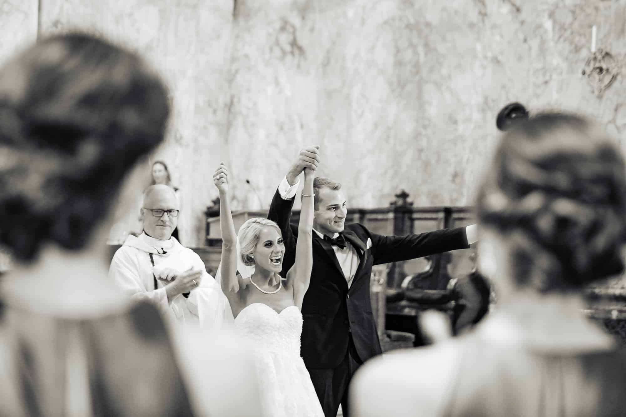 St. Patricks Church|bride and groom raising their arms with excitement after ceremony is over