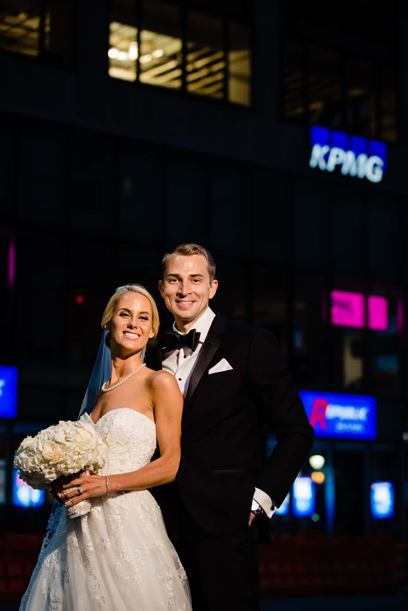 bride and groom in front of KPMG building
