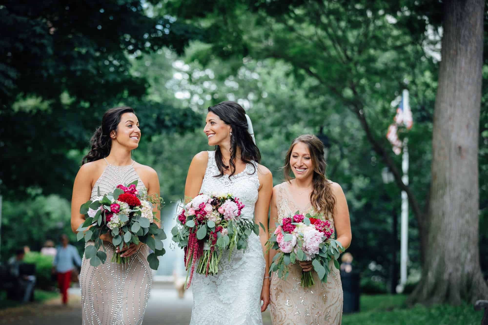 Bride and bridesmaids holding bouquets while walking