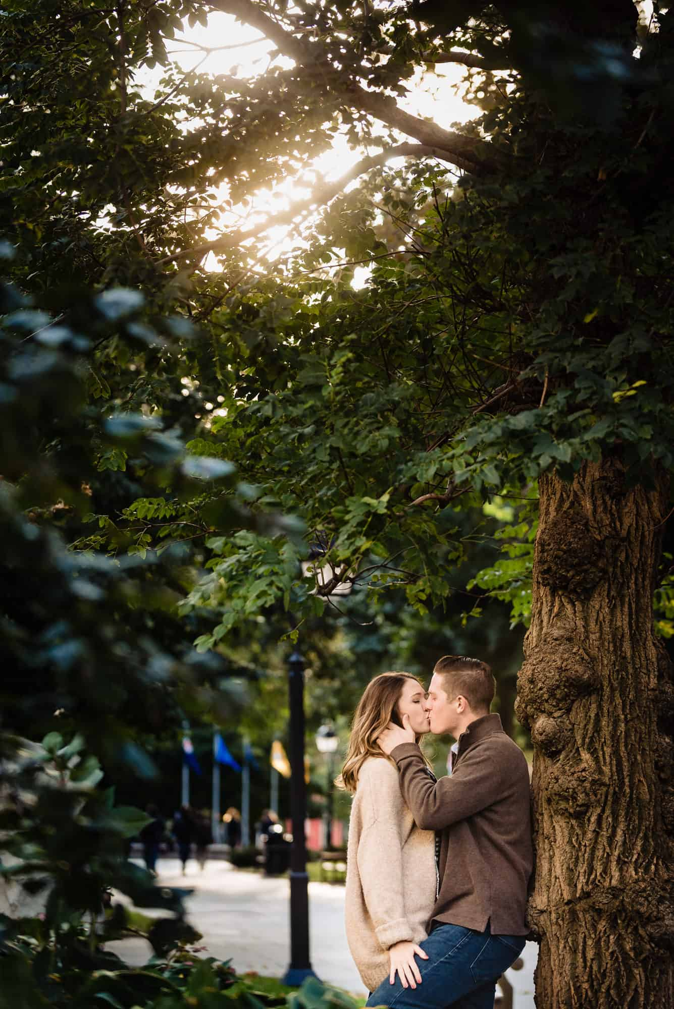 Couple kissing in front of tree in Washington Square Park
