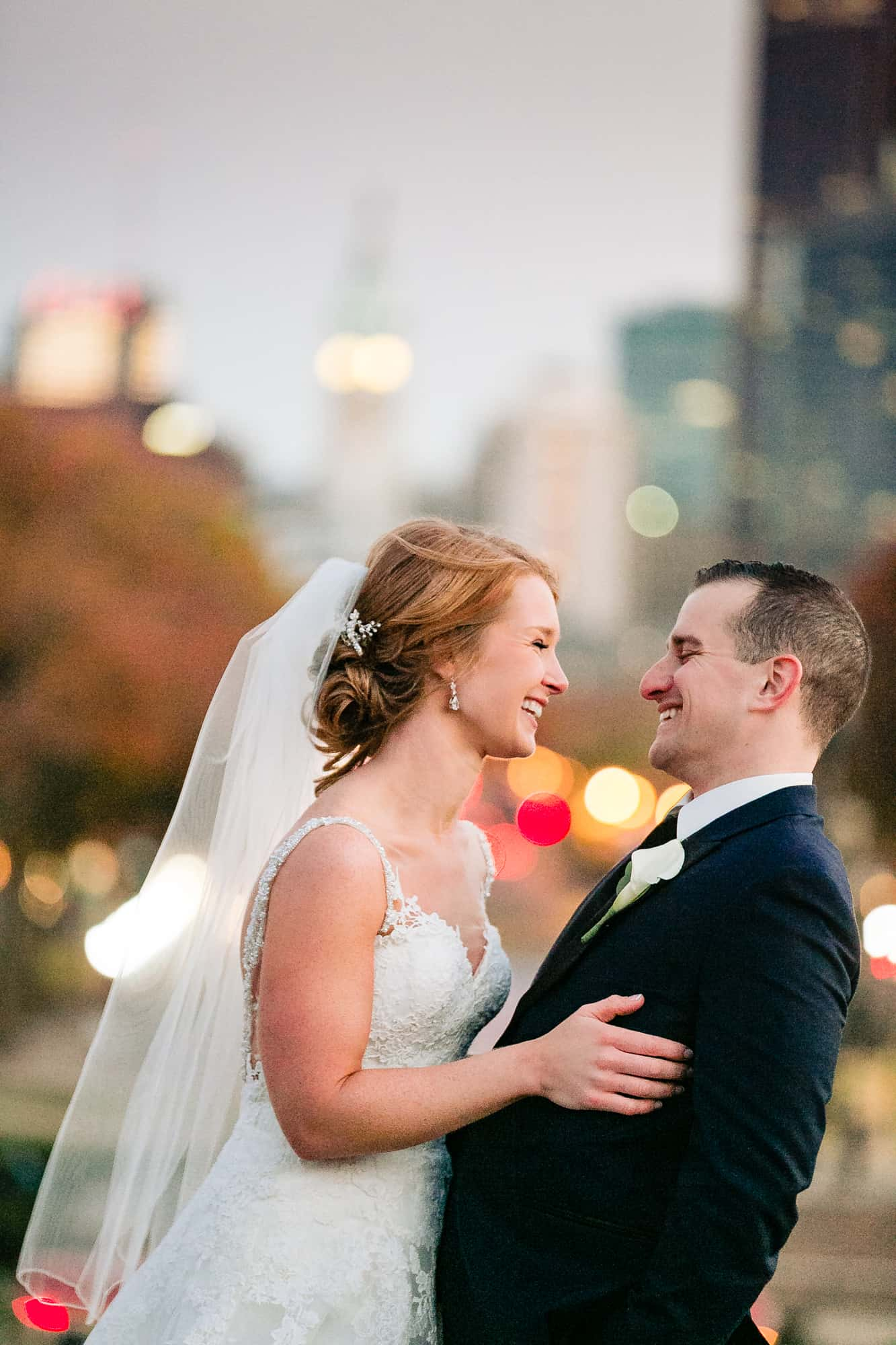 Bride and groom laughing with city lights behind them