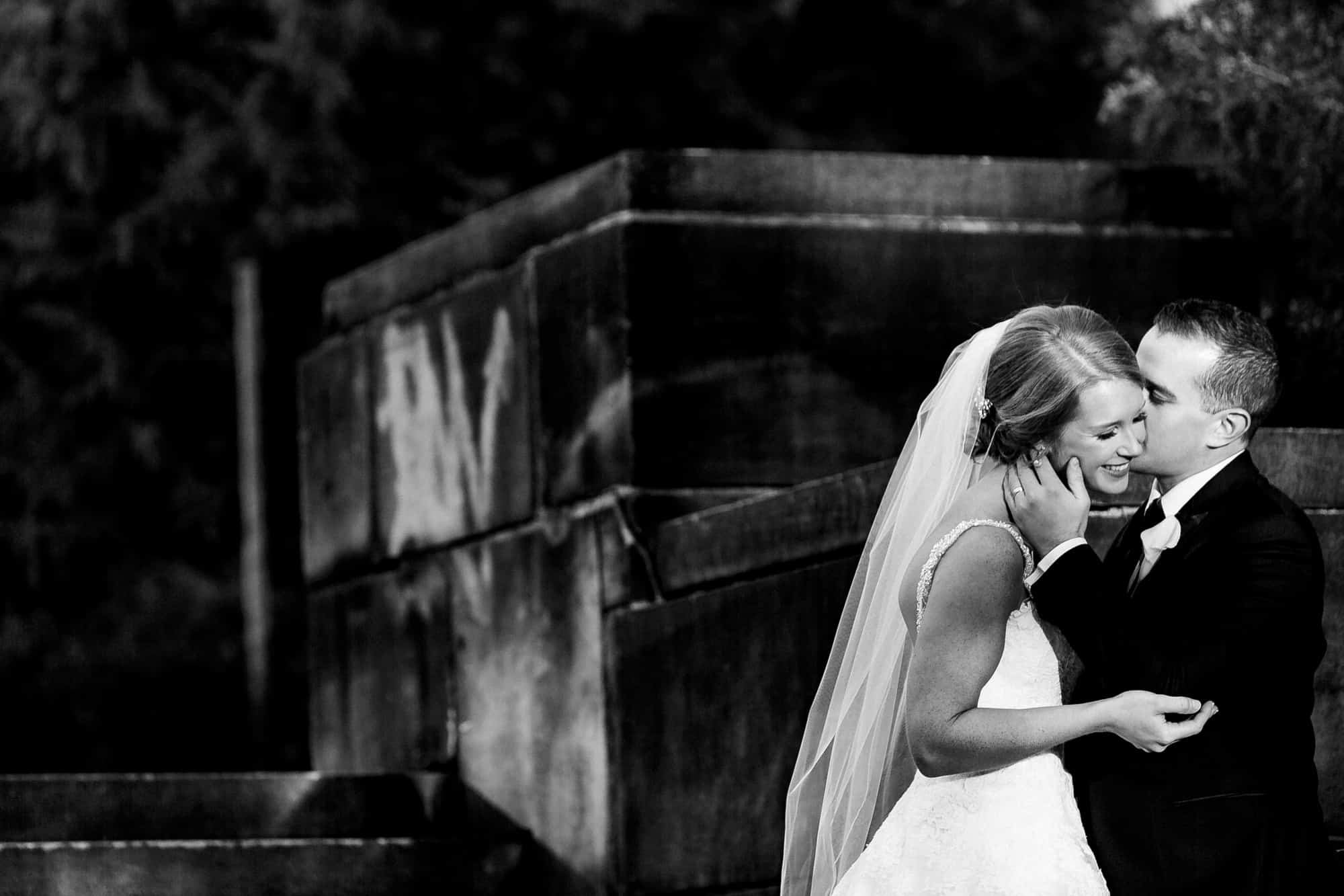 Black and white image of groom kissing brides cheek