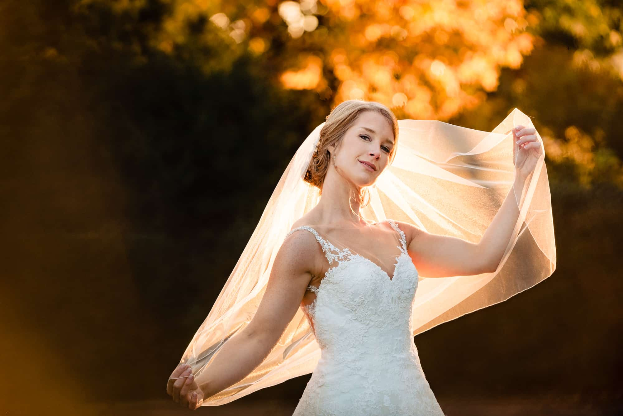 Bride playing with her veil at sunset