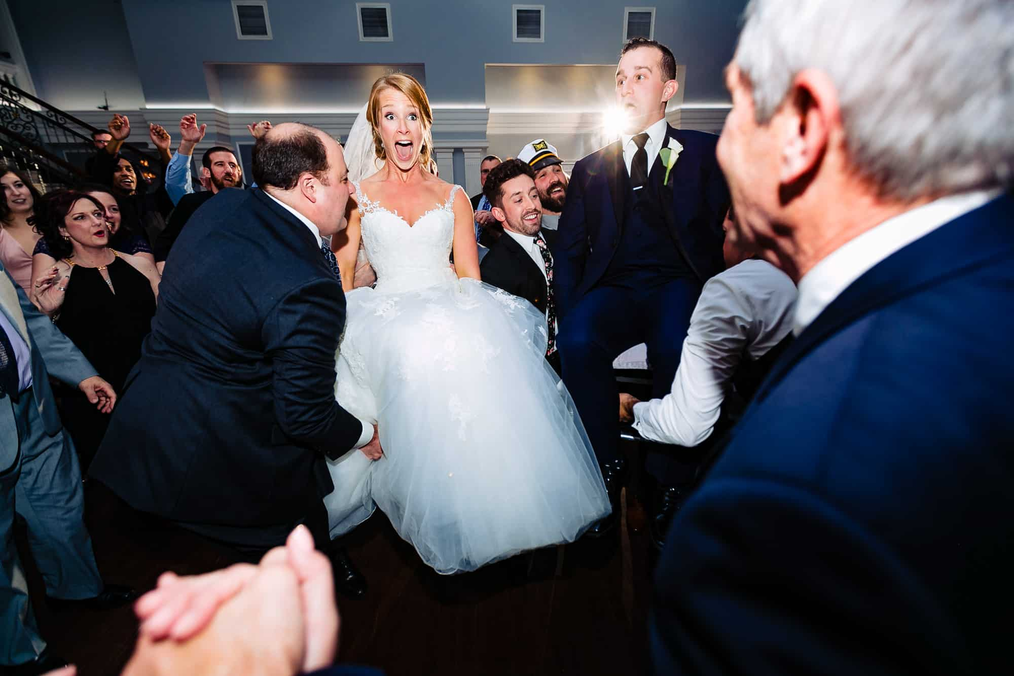 Bride being lifted in chair at the Arts Ballroom