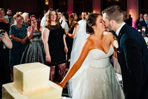 bride and groom kissing after cutting cake at the Loews Hotel in Philadelphia
