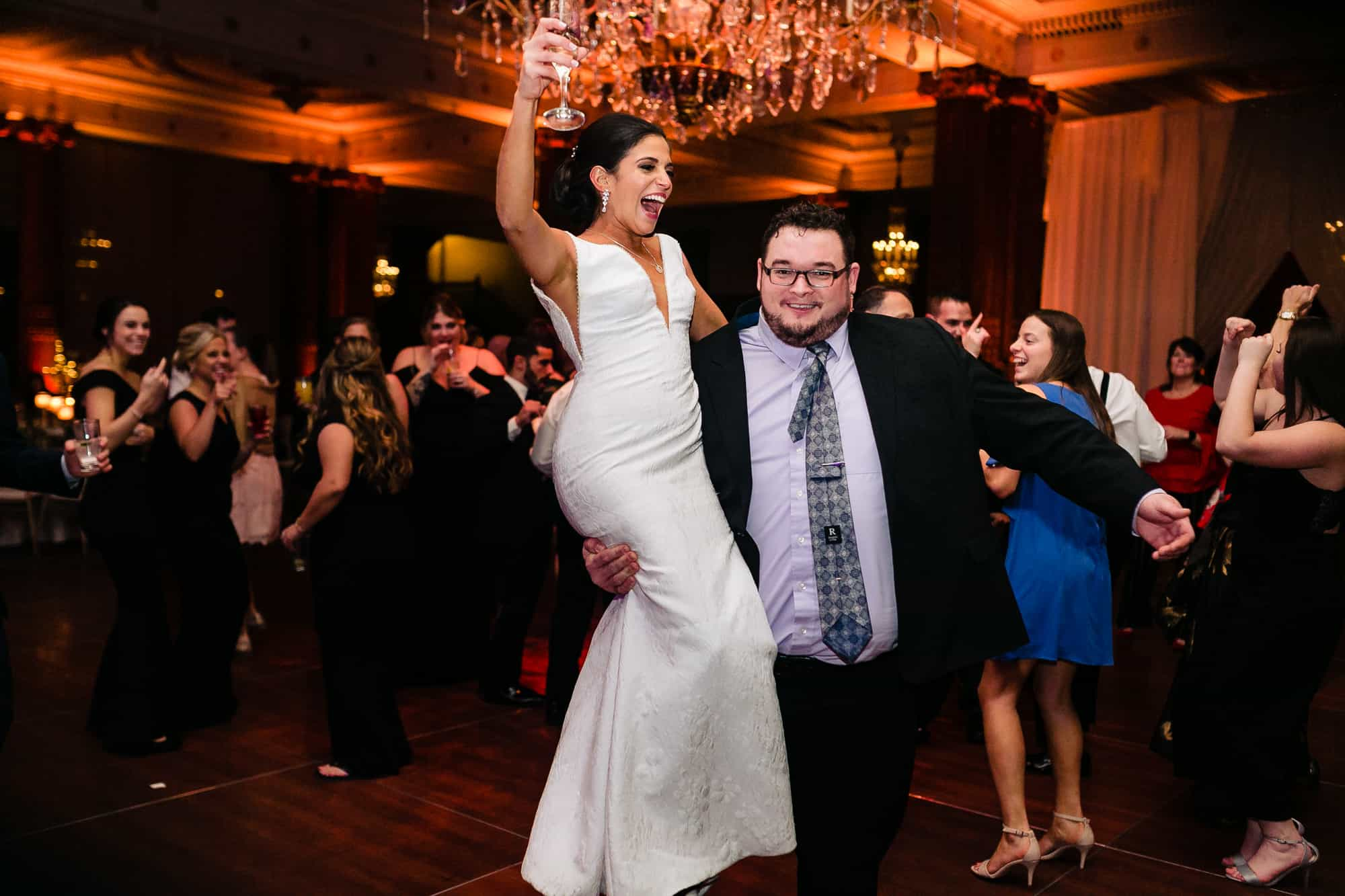 Bride being lifted up by guest at the Crystal tea Room in Philadelphia
