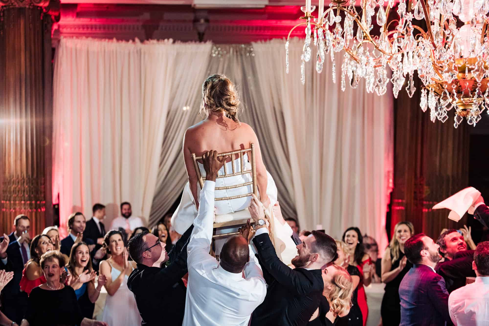Bride sitting in chair being lifted by friends at the Crystal Tea Room in Philadelphia