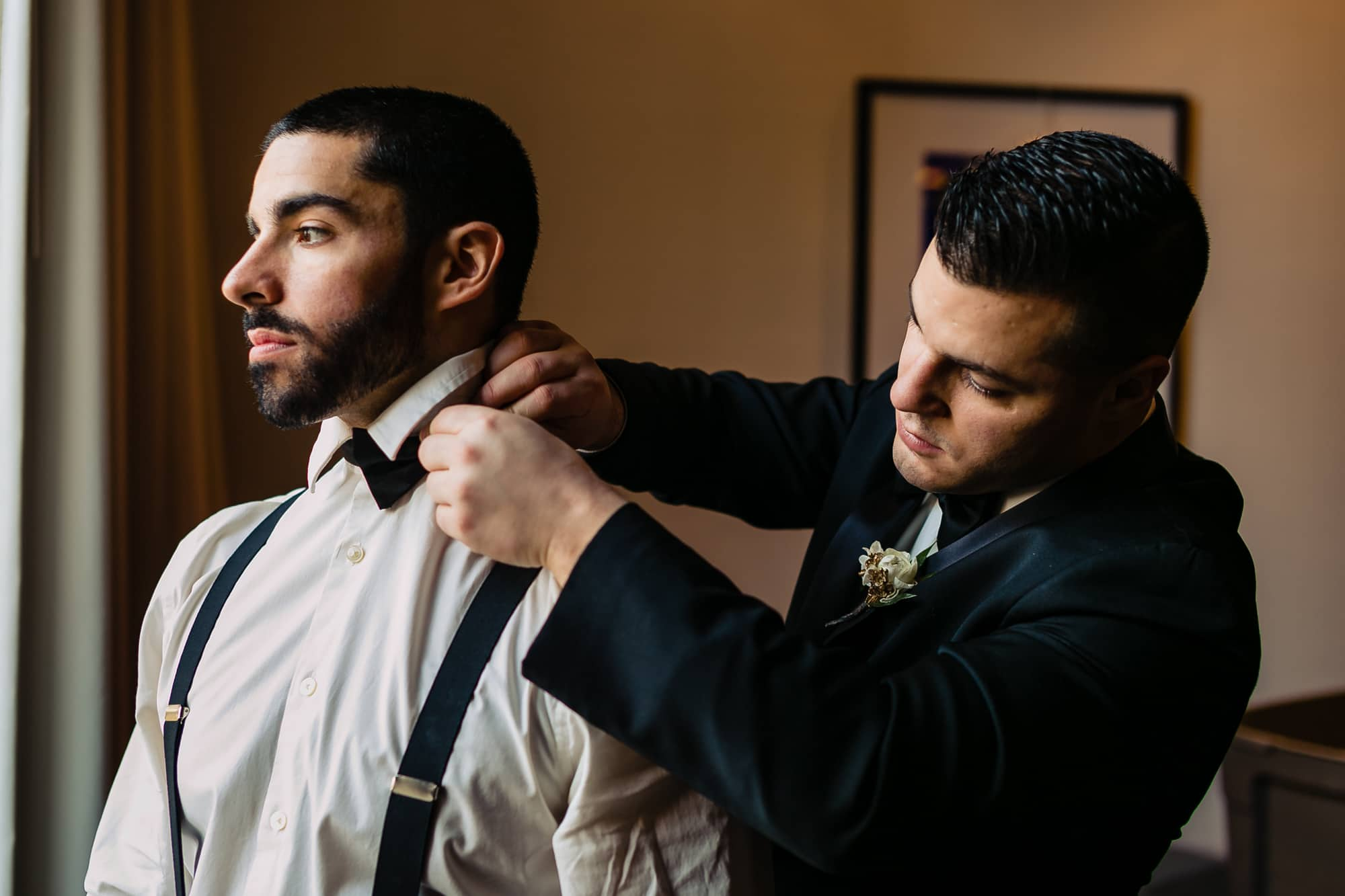 Groomsman helping groom adjust tie