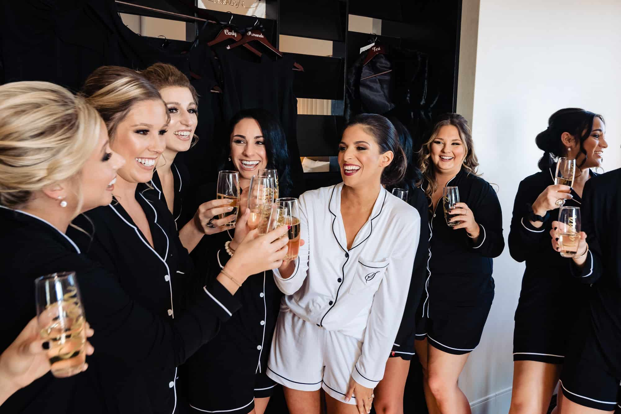 Bride toasts bridesmaids with champagne.