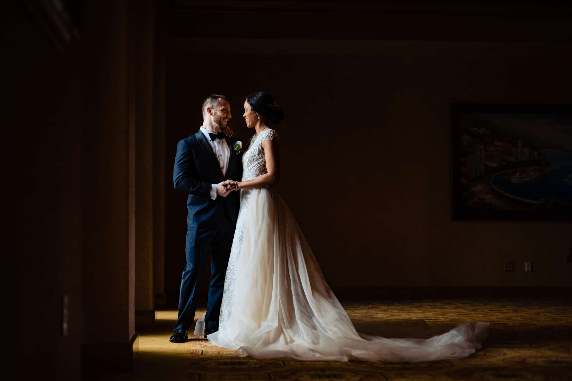 Bride and groom holding hands in beautiful window light