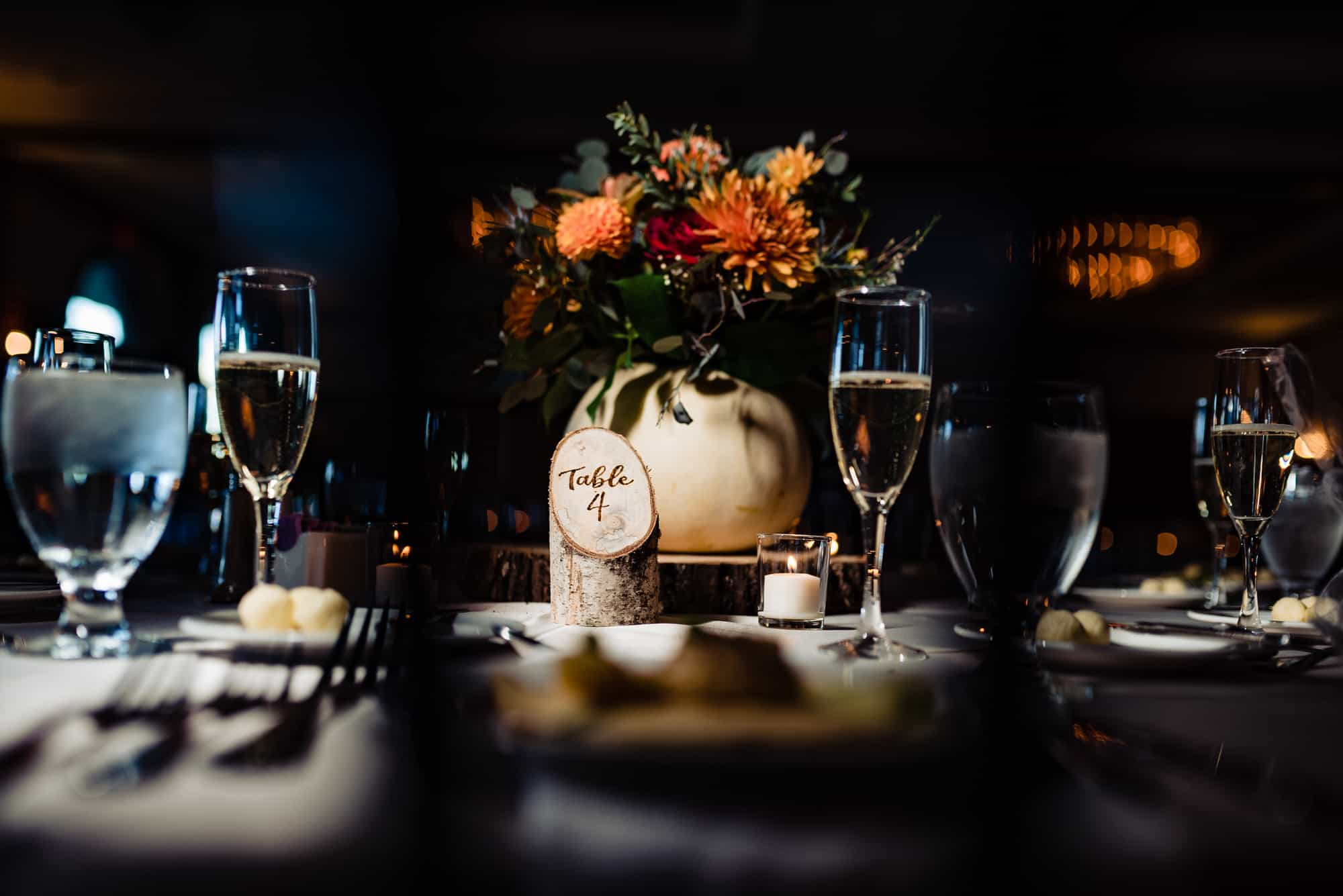 Fall wedding guest table decorations featuring flowers in a pumpkin