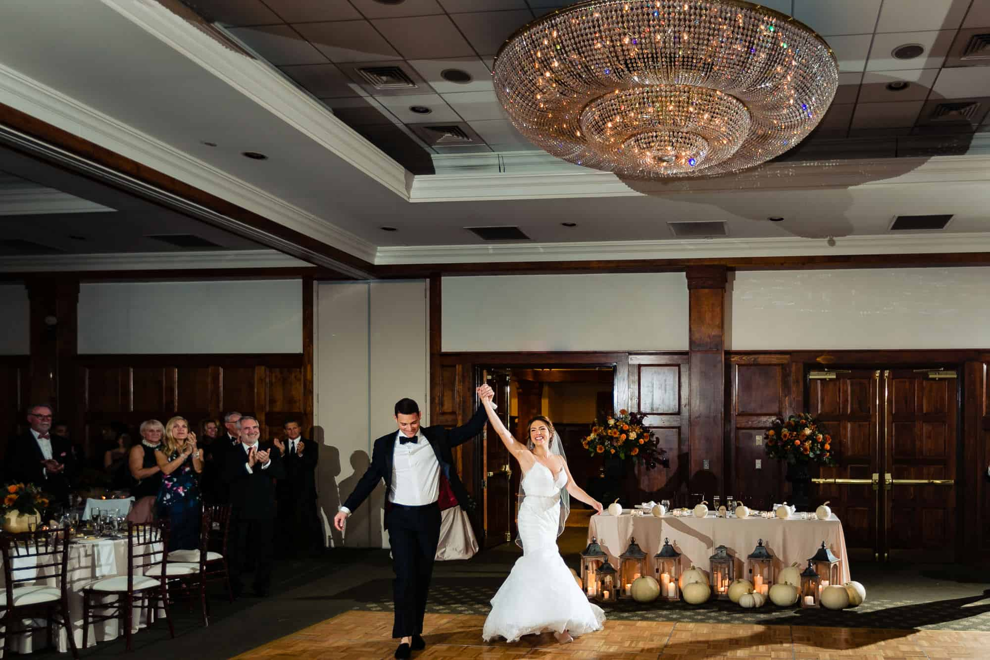 Bride and groom with arms raised as they walk into wedding recpetion