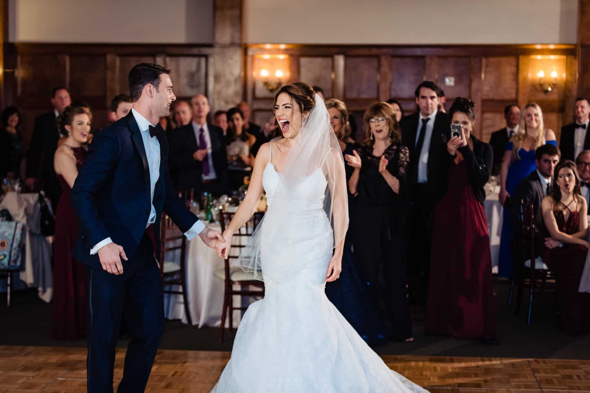 Bride laughing while holding grooms hand