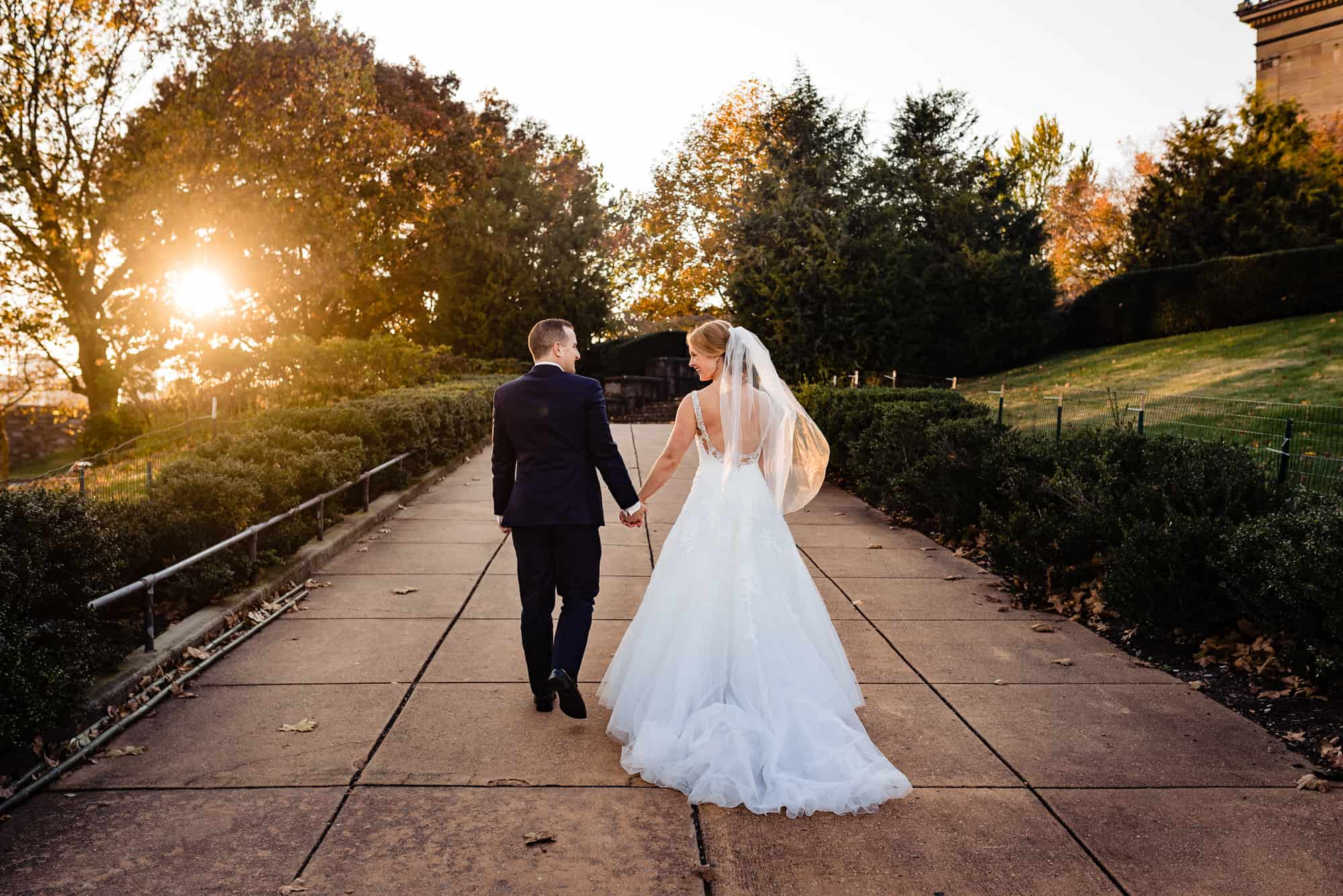 bride and groom walking hand in hand at sunset in epic wedding photo