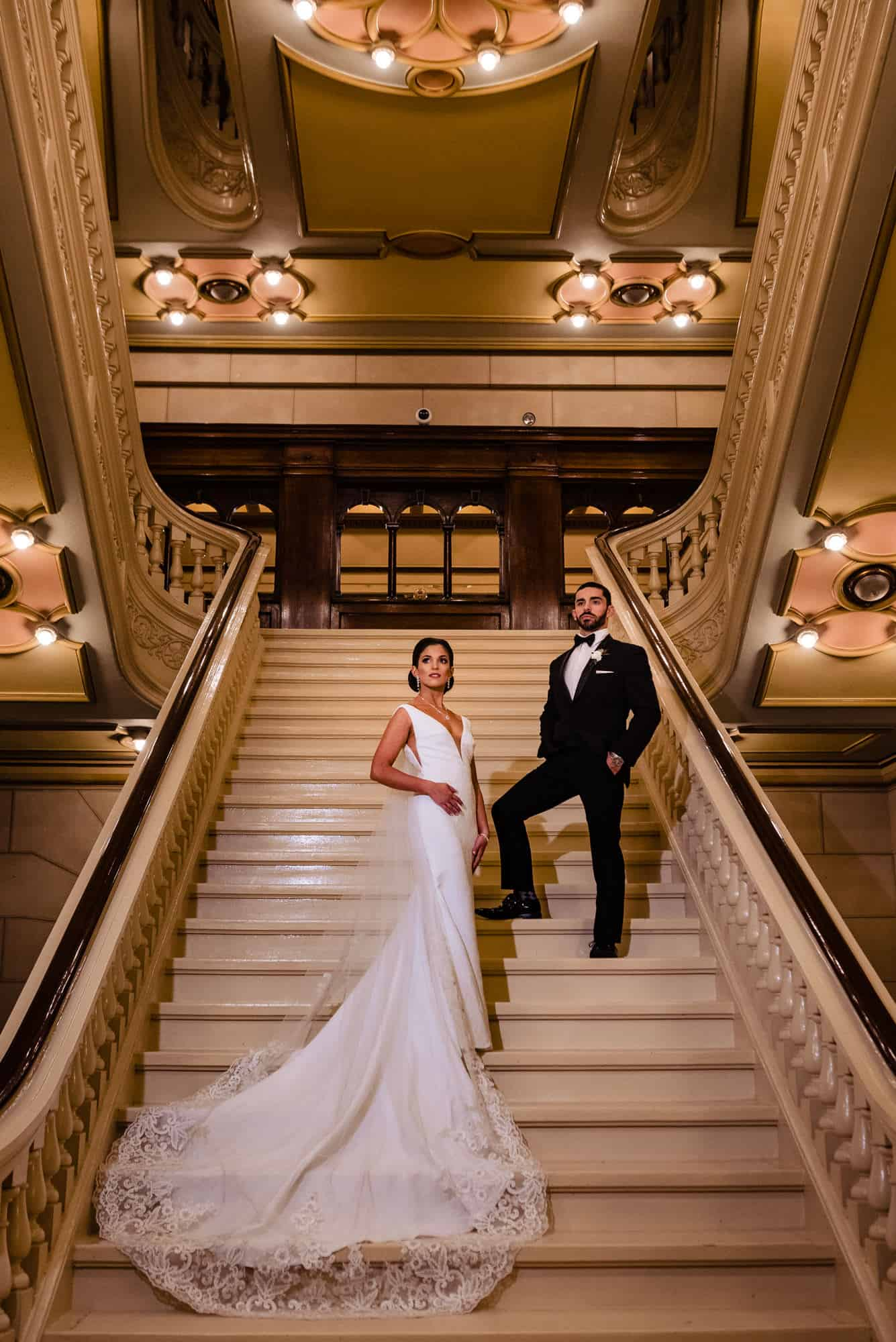 Bride and groom pose on Masonic Temple of Philadelphia stairwell