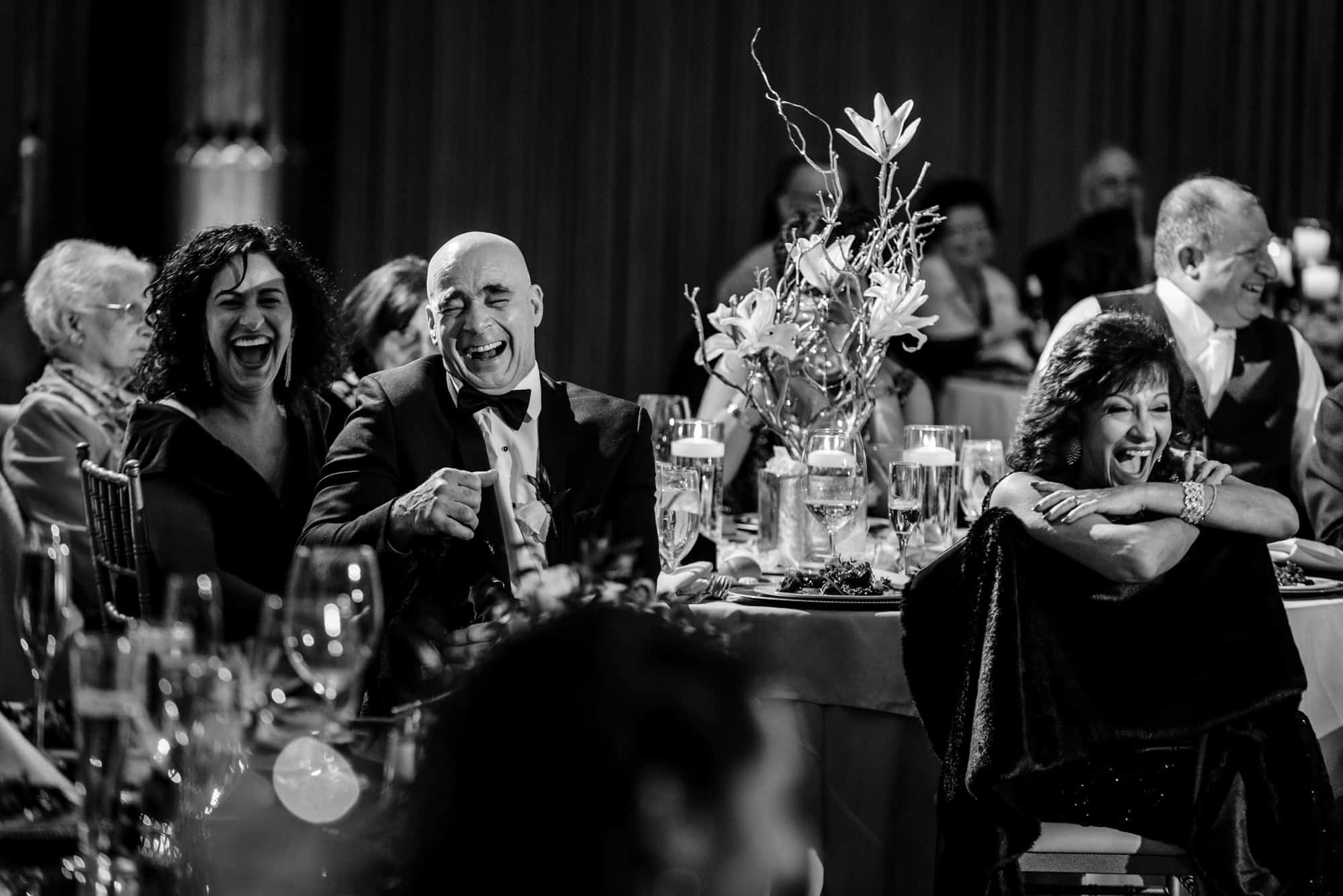Candid image of wedding reception guests laughing