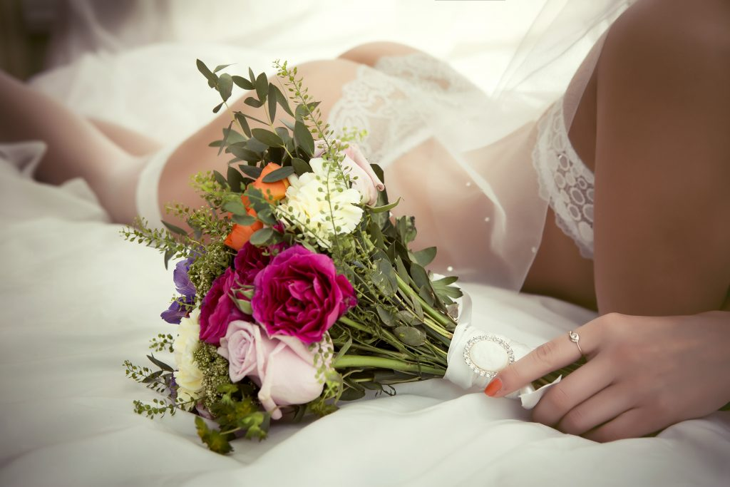 image of sexy woman in Bridal Boudoir holding colorful flowers