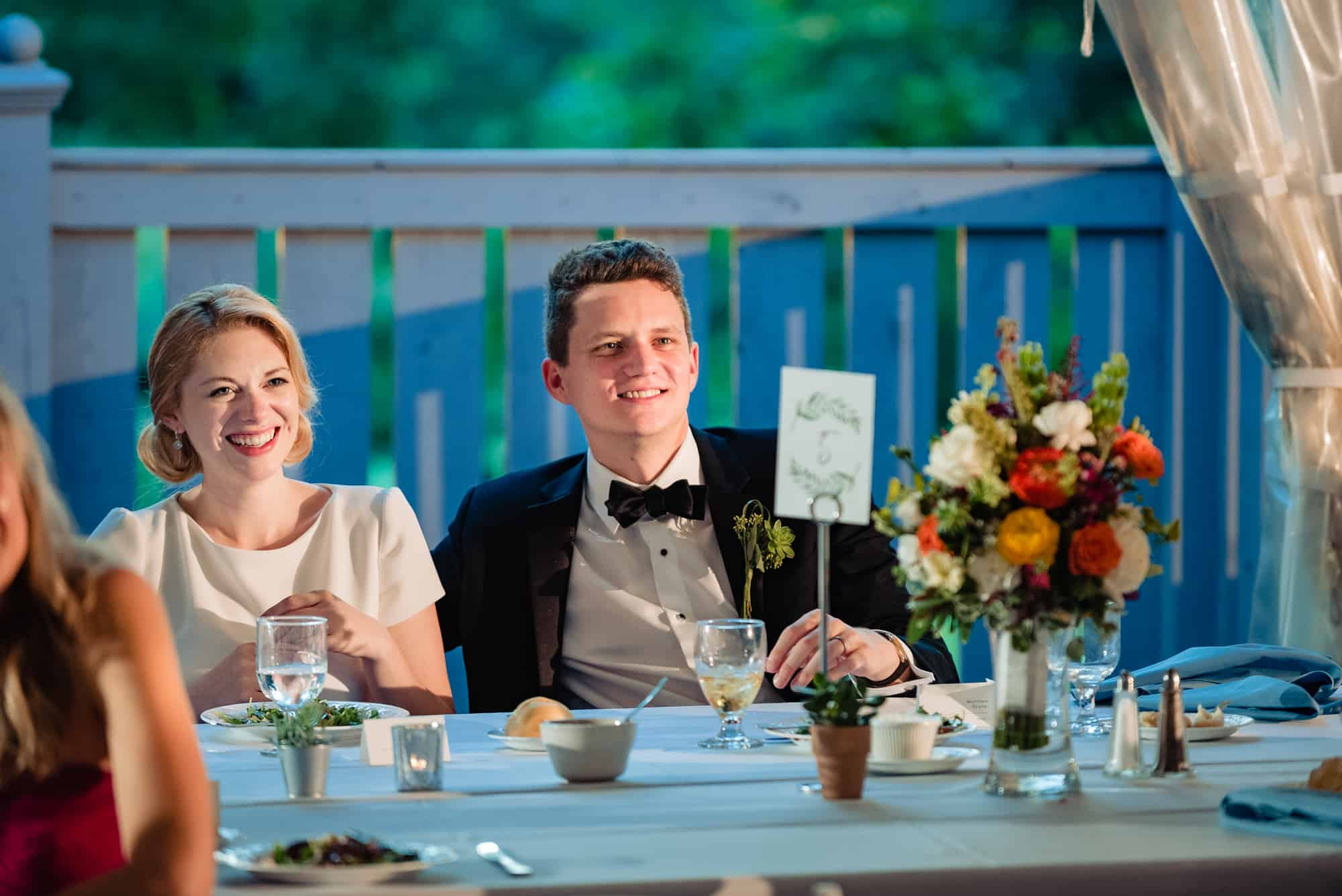 bride and groom laughing during toasts at their Morris Arboretum Wedding