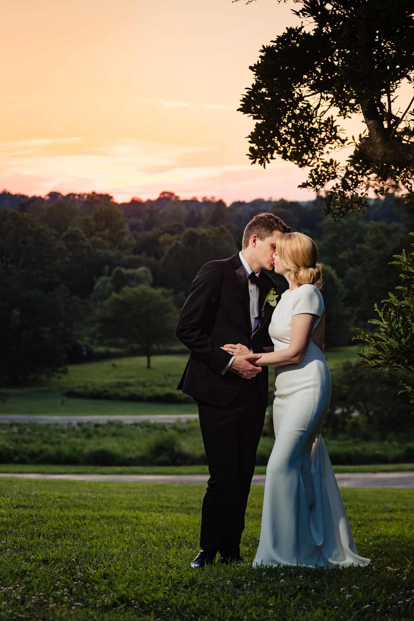 bride and groom kiss at sunset at their Morris Arboretum Wedding