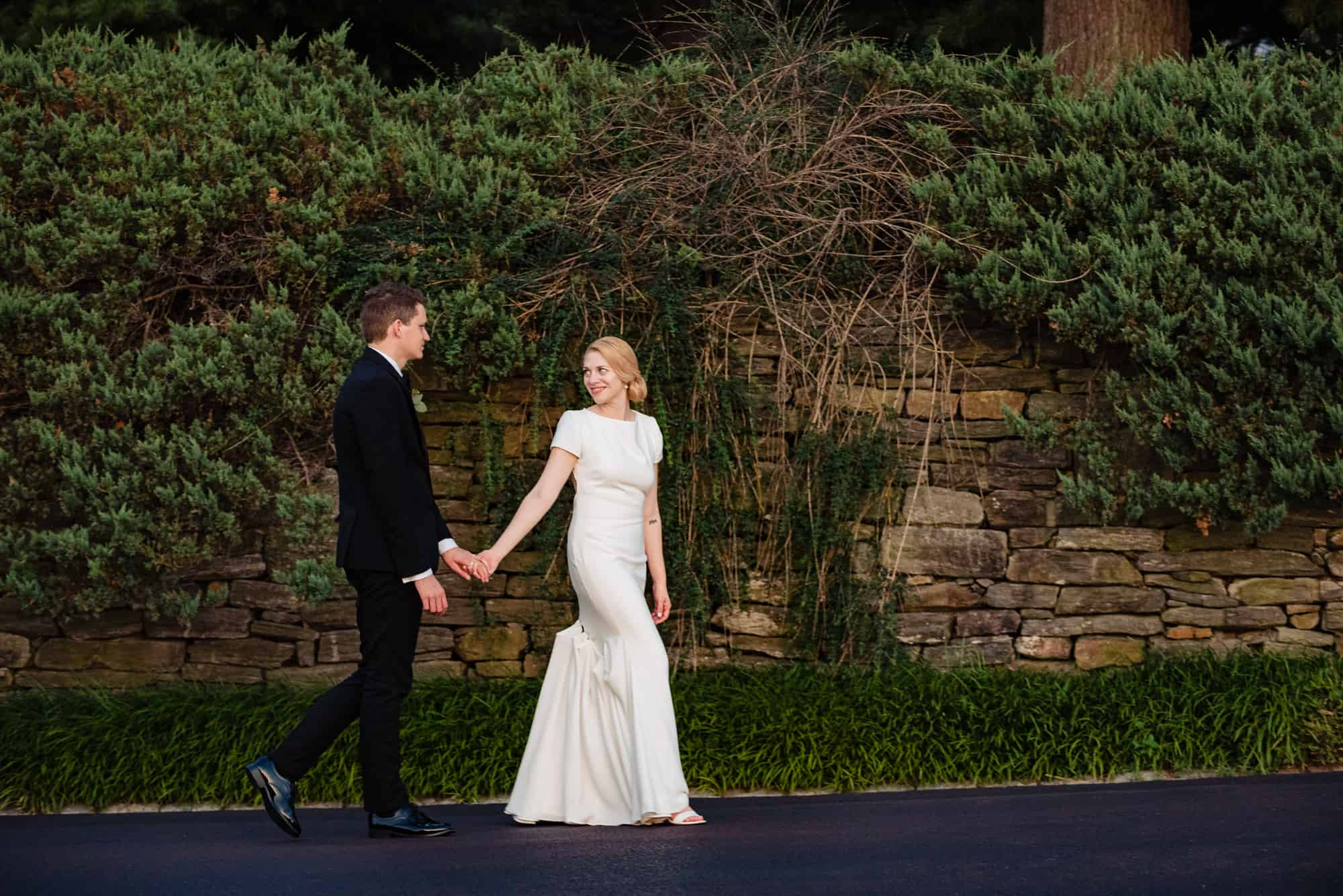 bride and groom holding hands and walking at their Morris Arboretum Wedding